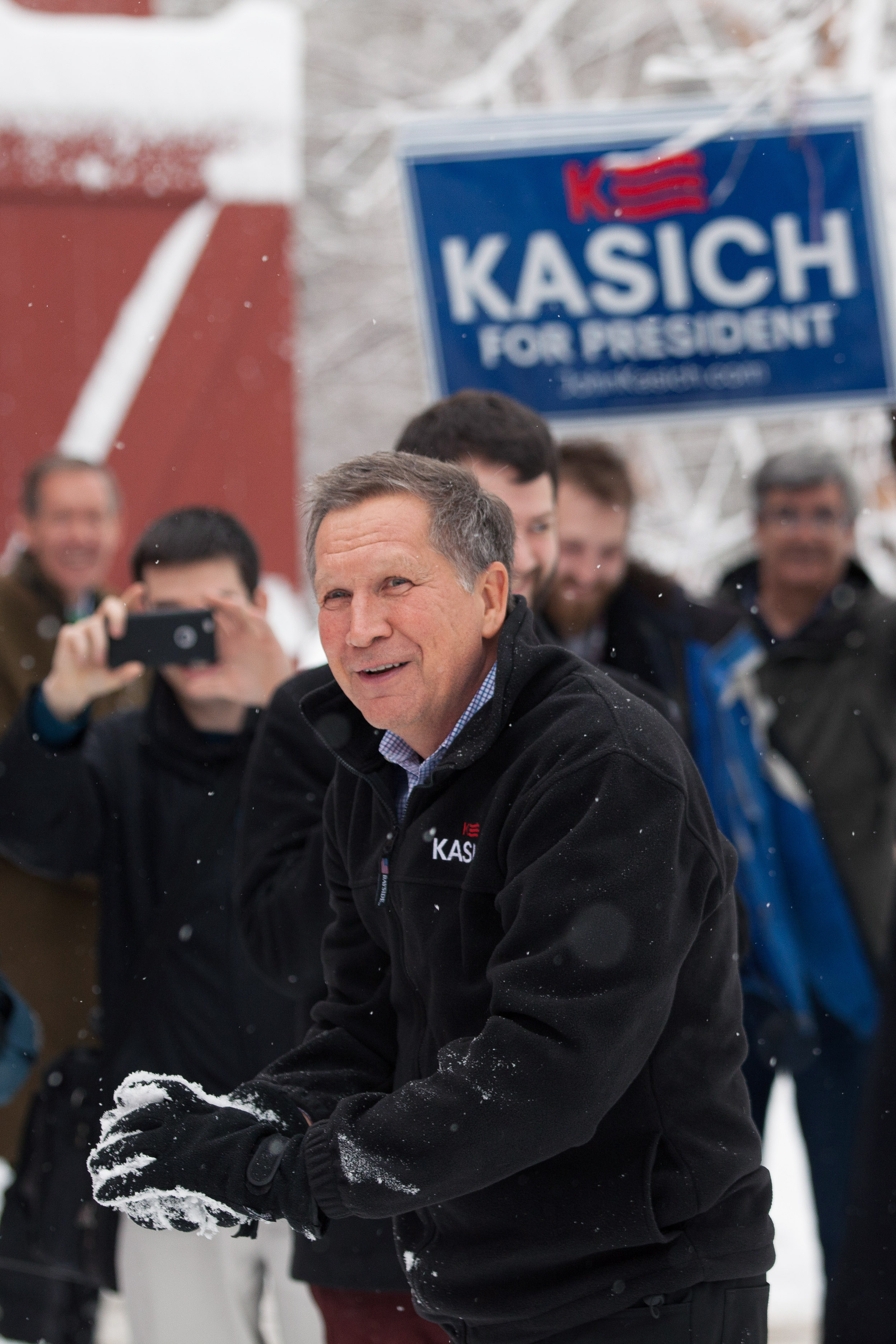John Kasich smiles during a snowball fight following a town hall on Feb. 5 in Hollis, N.H.