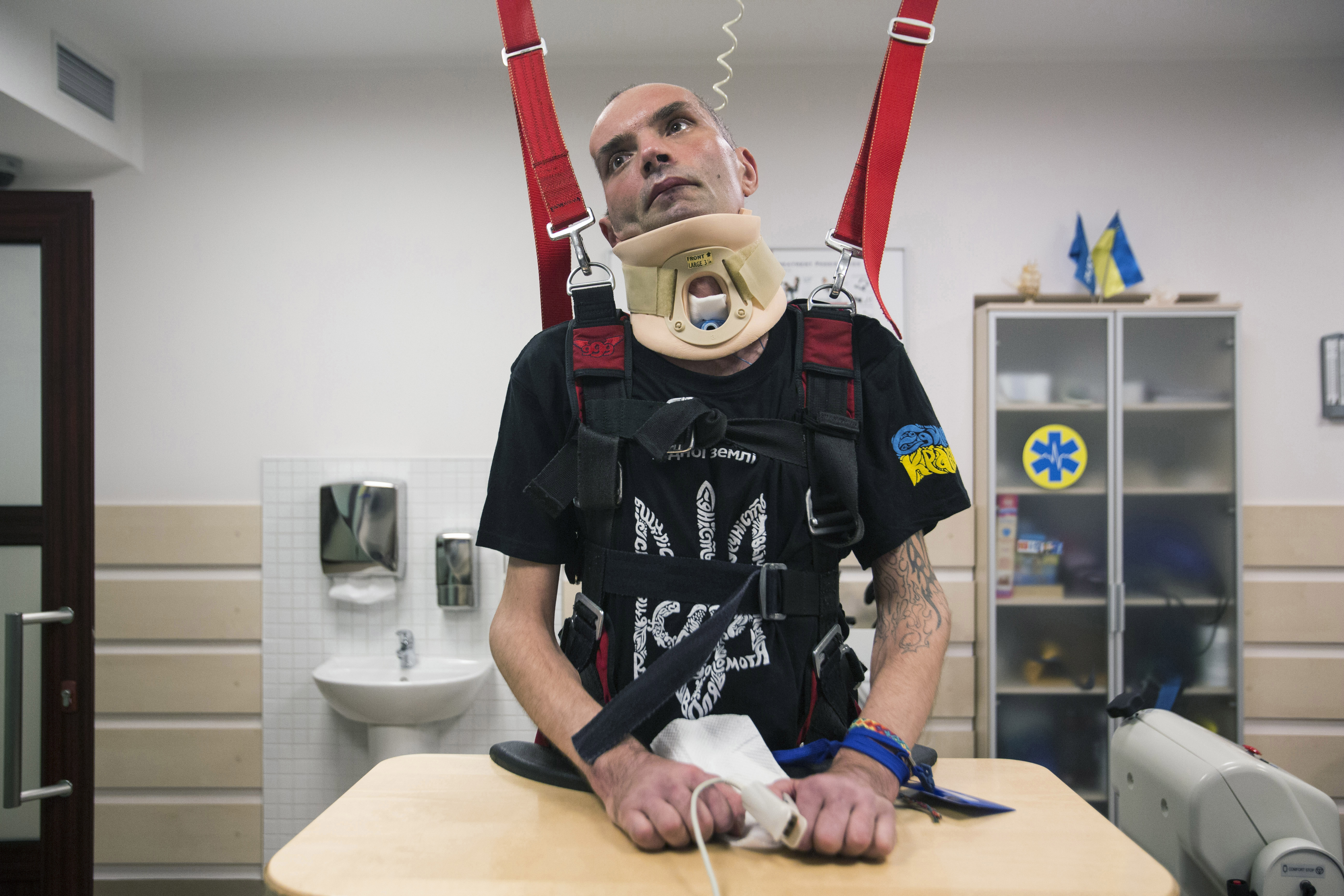 """Roman Kubishkin, a 41-year-old construction worker, is fastened and raised into a vertical position to simulate his feeling of space and balance at a rehabilitation center in Brovary, Ukraine, July 28, 2015. This helps stimulate his brain to begin communicating with his body. He breathes through a tube in his neck and is fed through another tube that carries food directly into his stomach. Kubishkin had joined the right-wing coalition Right Sector and was based in Pisky, a village near the remains of Donetsk International Airport, when shells fired by separatist forces nearly killed him on Jan. 22, 2015. His fellow soldiers thought he was dead due to a severe head trauma, in which Kubishkin lost much of the right side of his brain. """"Sixteen clinics refused to take Roman because he was in such difficult condition. Nodus was the only one,"""" said his mother, Iryna, referring to the modern neurological and neurosurgical rehabilitation center in Brovary, outside Kiev. His monthly care costs about $3,000 to $3,300, which is largely funded by donations and volunteers."""