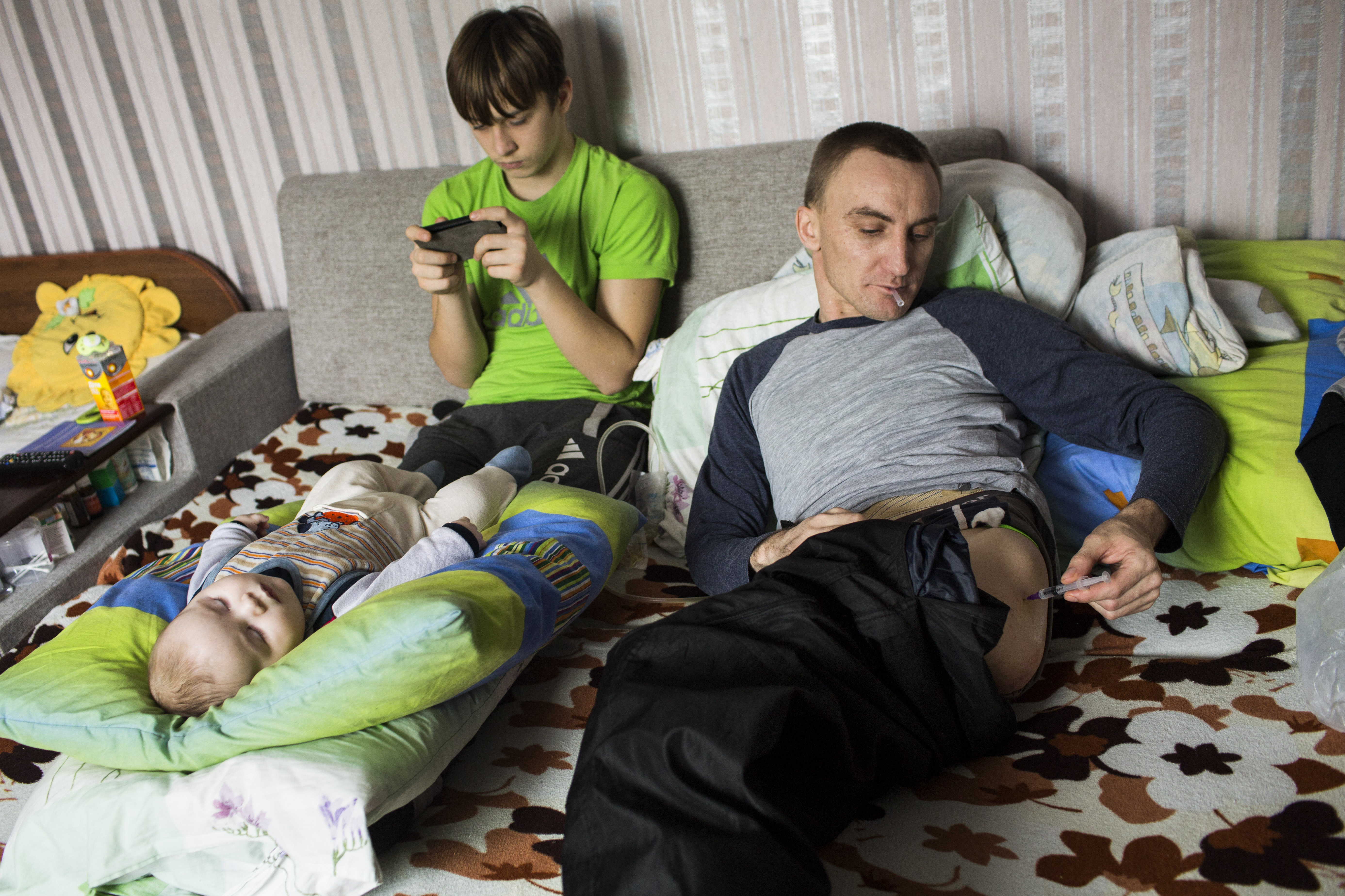 """Honcharovsky administers a dose of nalbuphine, a powerful painkiller, as his infant son, Nazar, sleeps in their home in Teofipol, Ukraine, Feb. 6, 2015. A daily dose consists of one or two injections. At times, he administers up to six injections in a day. """"I taught myself how to give injections so I don't wake up my son, wife or mother in the middle of the night,"""" he said."""
