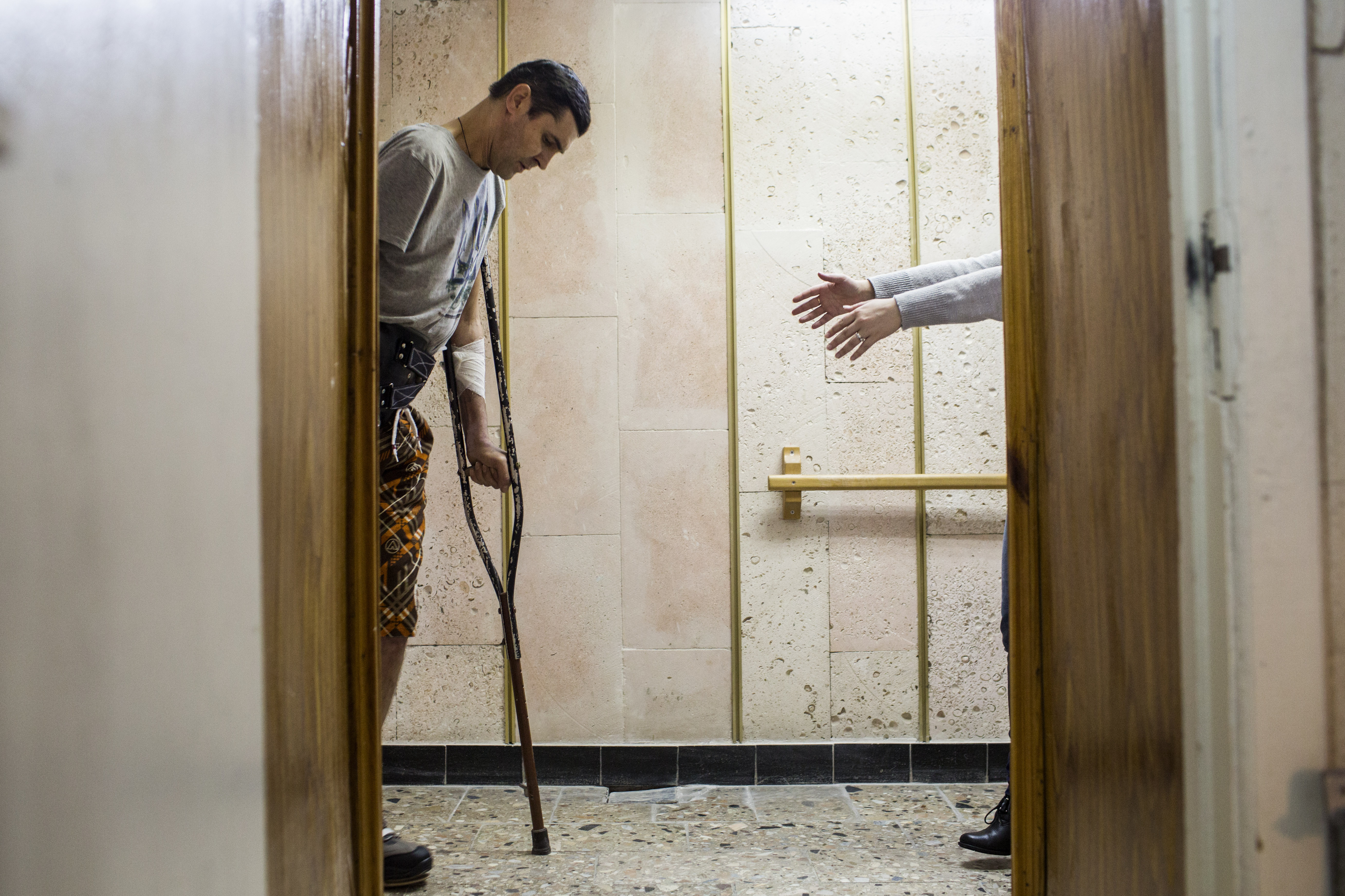 Viacheslav Buinovsky, 41, walks toward a close friend as he takes some of his first steps using a prosthetic leg at Ortotech Service, a prosthetics workshop in Kiev, Ukraine, Feb. 10, 2015. Buinovsky worked as a mechanic in Sumy Oblast prior to the Euromaidan revolution, in which he took an active role. He joined the Aidar Battalion, a volunteer unit, after the revolution and was severely wounded near Luhansk in September 2014. His right hand and right leg were amputated.  I would like to return to fight, but I do not have the ability,  he said.  What I can do to contribute from here, I will do. Everyone who was there would like to return back ... but not everyone can.