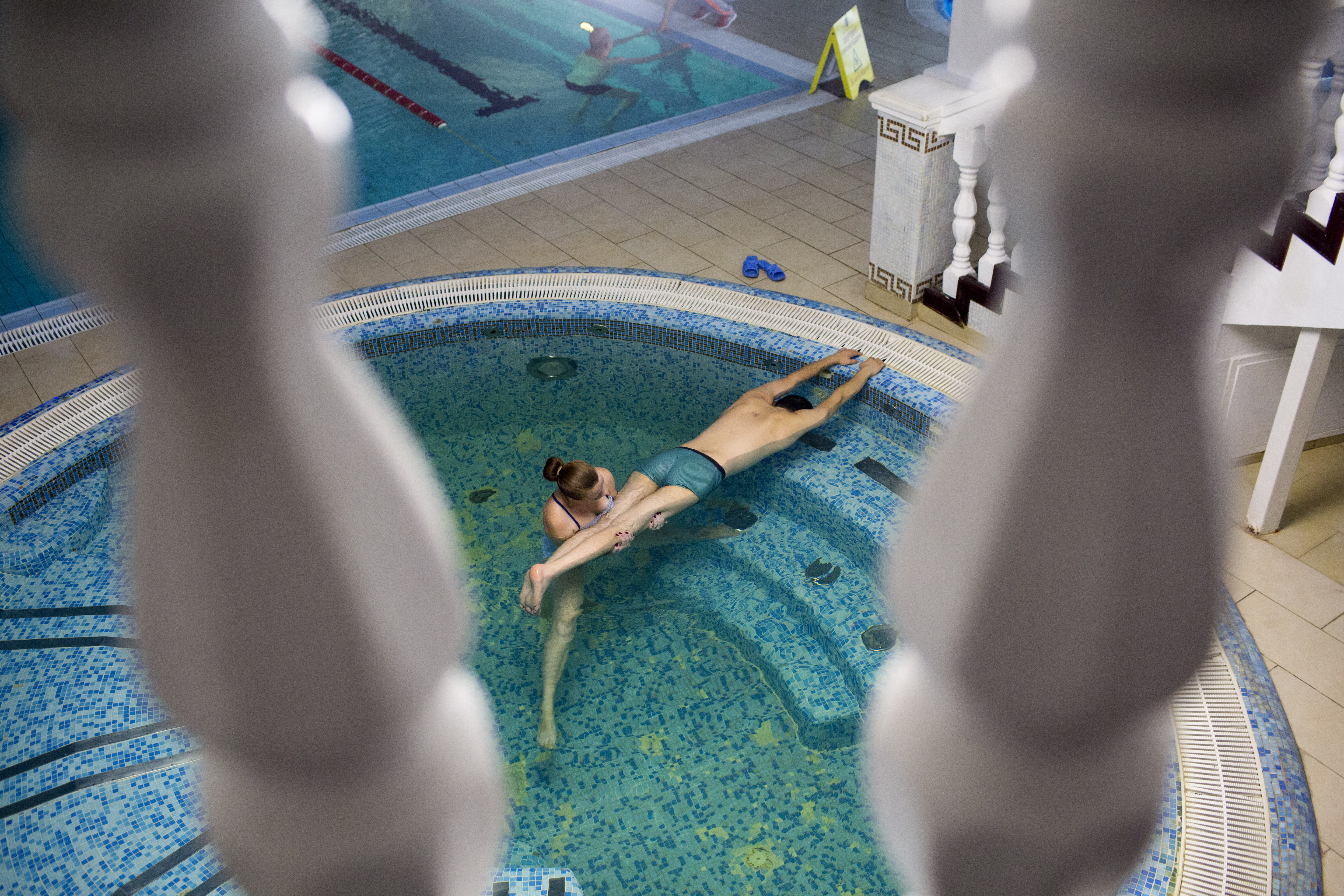 """Artem Zapototsky, 34, undergoes physical therapy in a pool in Truskavets, Ukraine, Sept. 6, 2014. The married father of two was severely wounded during the Euromaidan revolution on Feb. 20, 2014, when he was shot in the back as he stood unarmed on the footbridge that crosses above Instytutska Street. The bullet damaged his spine before embedding near his left shoulder blade, where it remains today. Zapototsky is a lawyer from Lutsk, in the country's northwest; he aspires to regain the use of his legs and trains for approximately six hours a day while continuing his legal work. """"I am just very thankful that I already have children,"""" he said. """"I cannot imagine myself not walking again."""""""