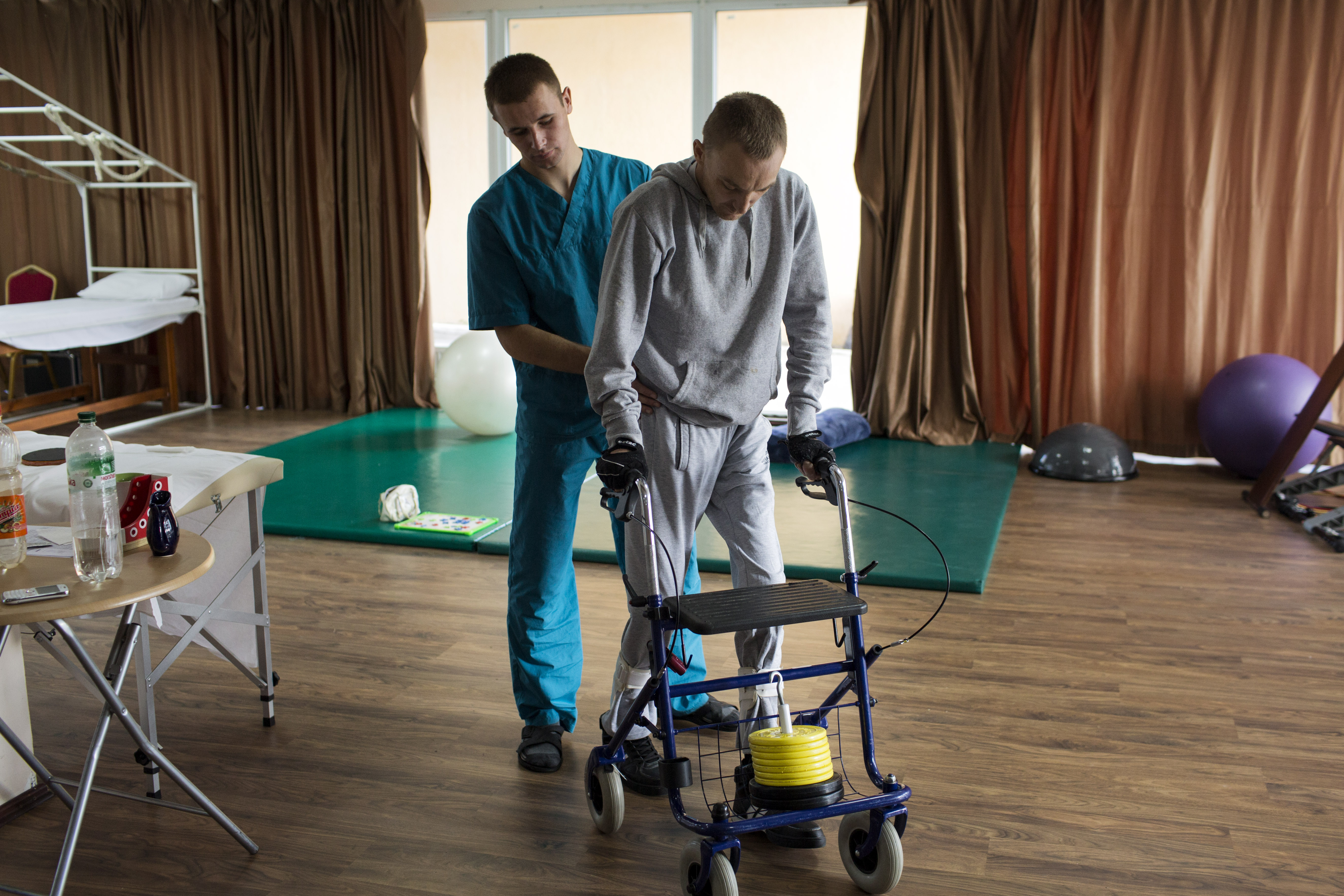 """Volodymyr Honcharovsky, 31, a married father of four children, works with a physical therapist at a training center in Truskavets, Ukraine, Oct. 6, 2014. He was severely wounded on Feb. 20, 2014, when he was shot three times—twice in the back, once in the right arm—while attempting to reach wounded demonstrators who had been shot by security forces during the Euromaidan revolution in Kiev. Honcharovsky has feeling in his legs and can take small steps for short distances, but his legs have atrophied. Often, it is extremely difficult for him to walk due to extreme pain caused by nerve damage. """"I pray and place my hope in the Lord that he will help me to stand on my legs,"""" he said."""