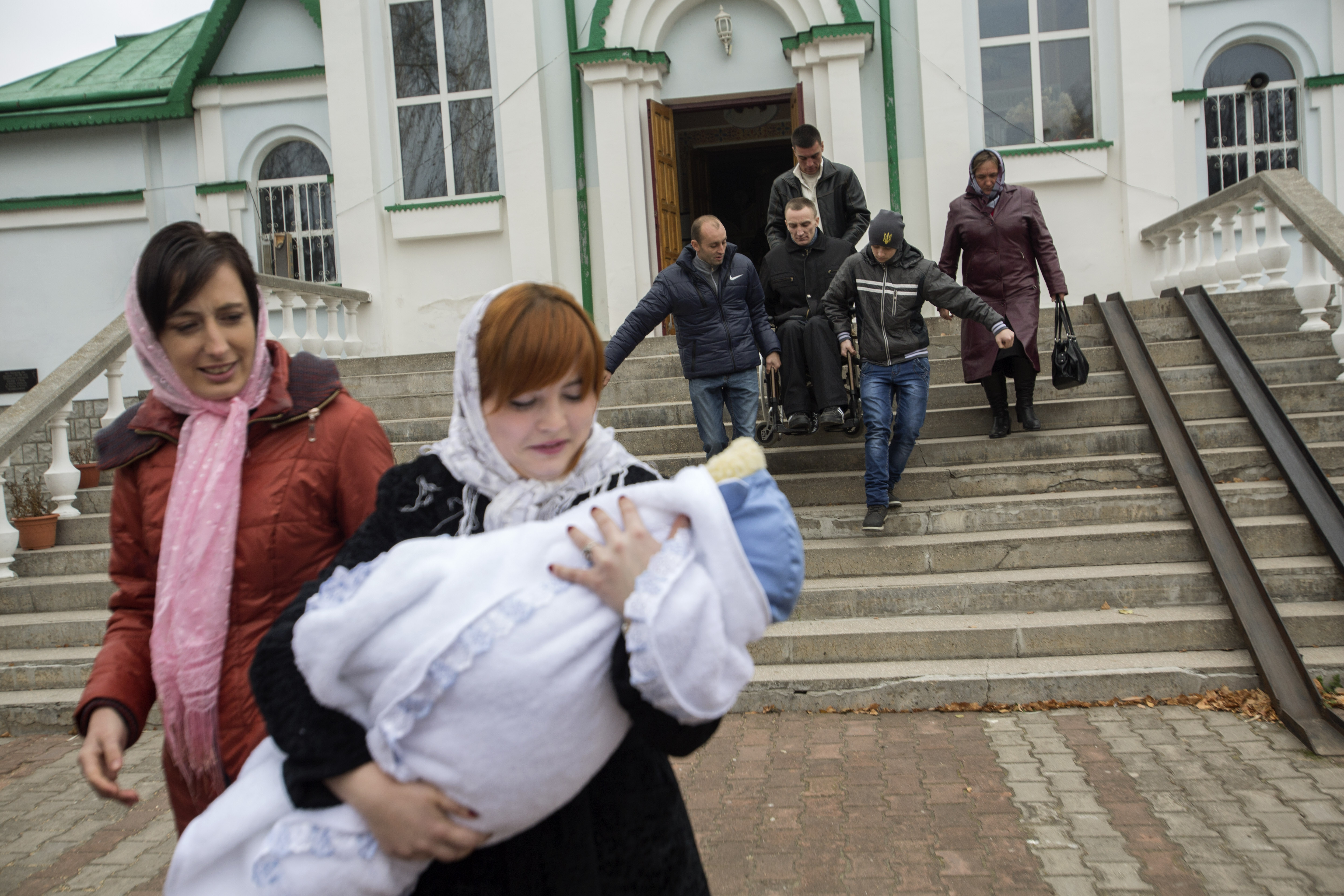Honcharovsky is assisted down a set of stairs after his son's christening at a church in Teofipol, Ukraine, Nov. 16, 2014. Proper infrastructure for the physically disabled barely exists in some Ukrainian cities, towns and villages.