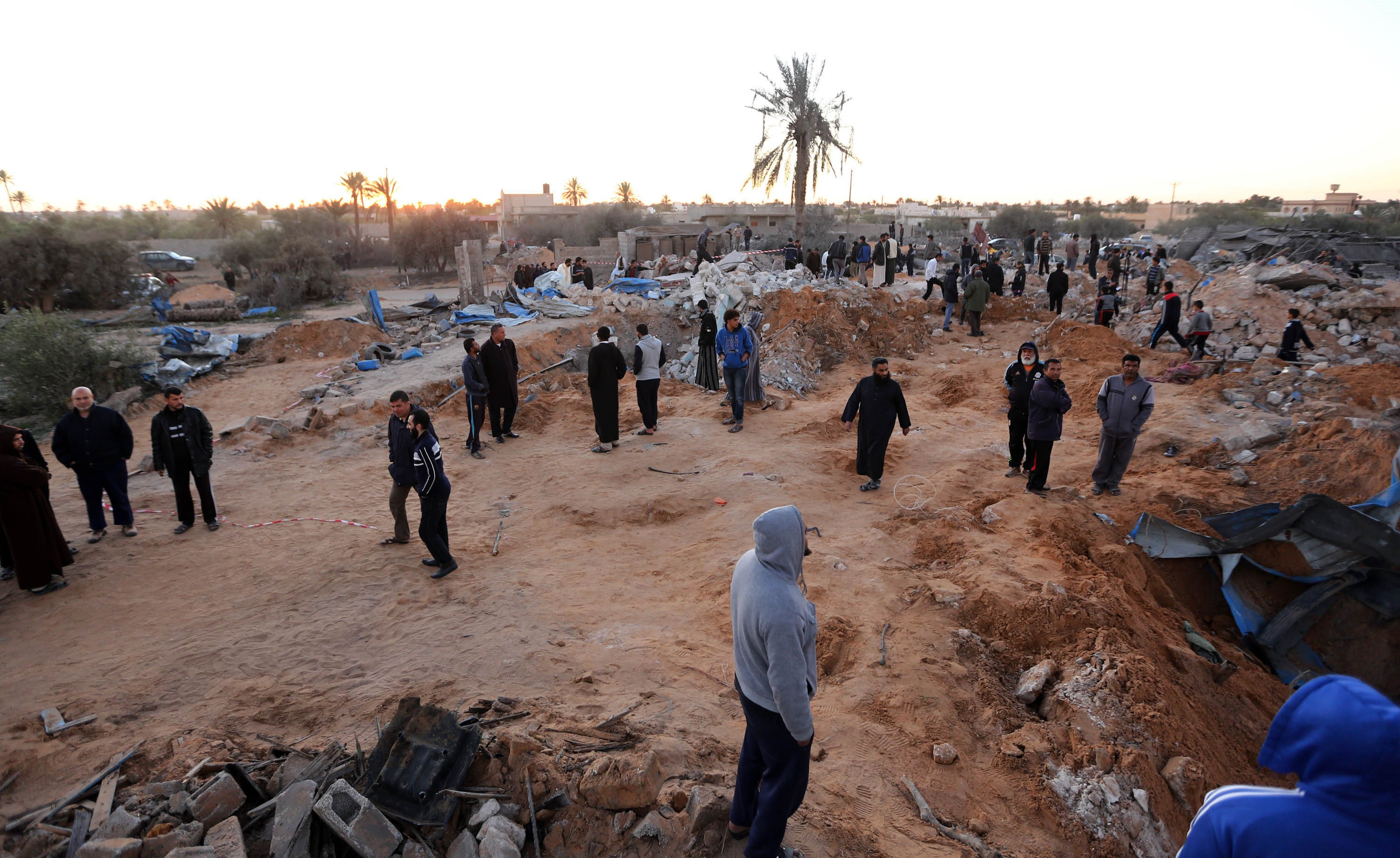 People gather around a damaged area after U.S. warplanes carried out air strikes against Daesh training camp in western Libya on Feb. 19, 2016.