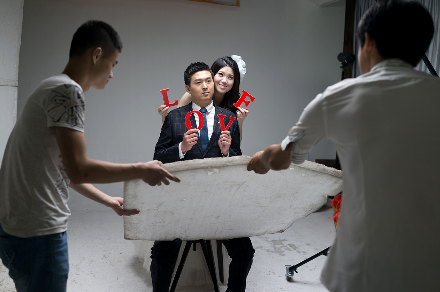 A couple is photographed in June 2015 at Inside Only Photo Studio on the outskirts of Shanghai. The studio houses three floors of sets for wedding photos, including rooms of dresses and suits.