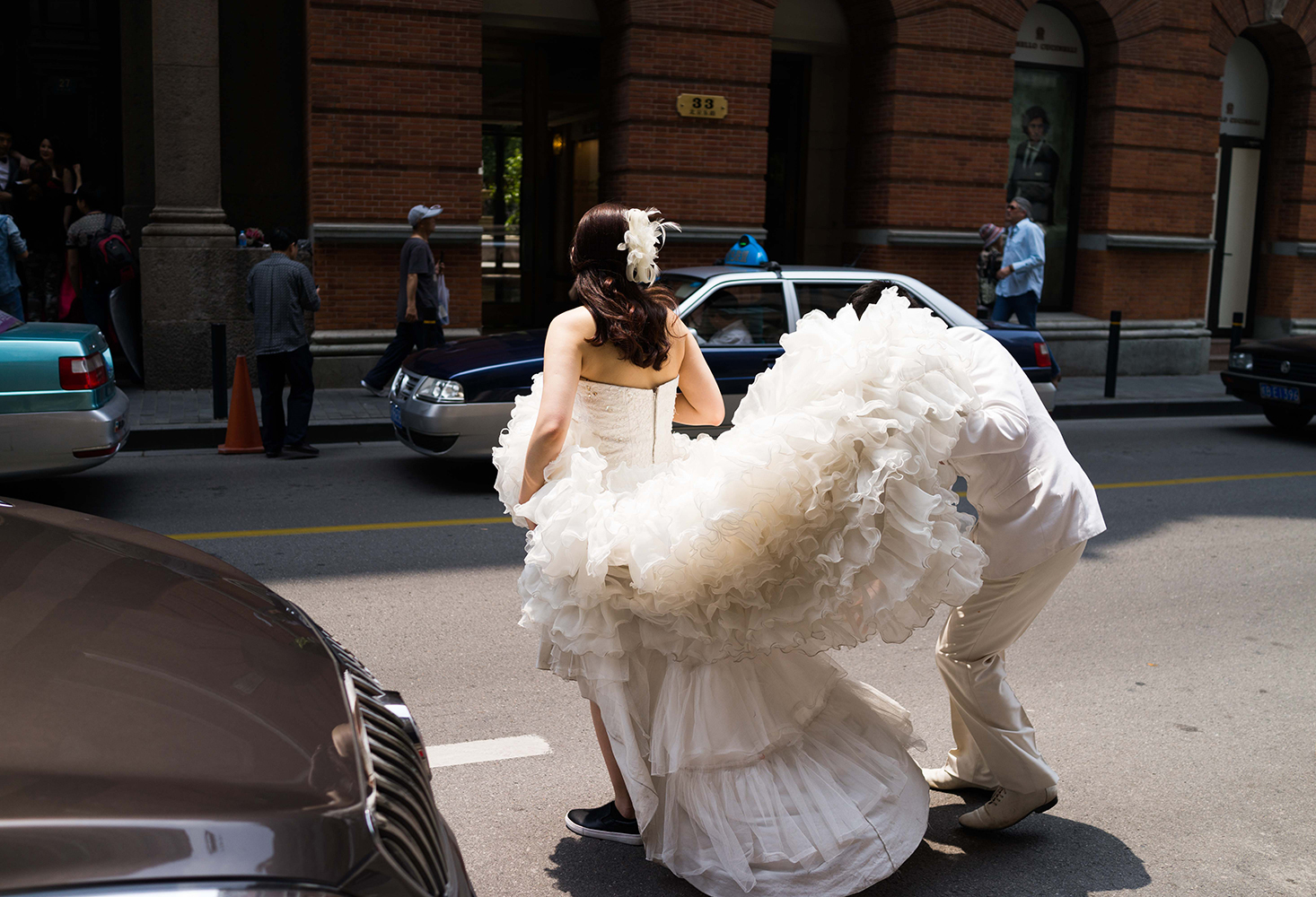 A bride-to-be has her dress adjusted during a photo shoot in Shanghai in May 2015.