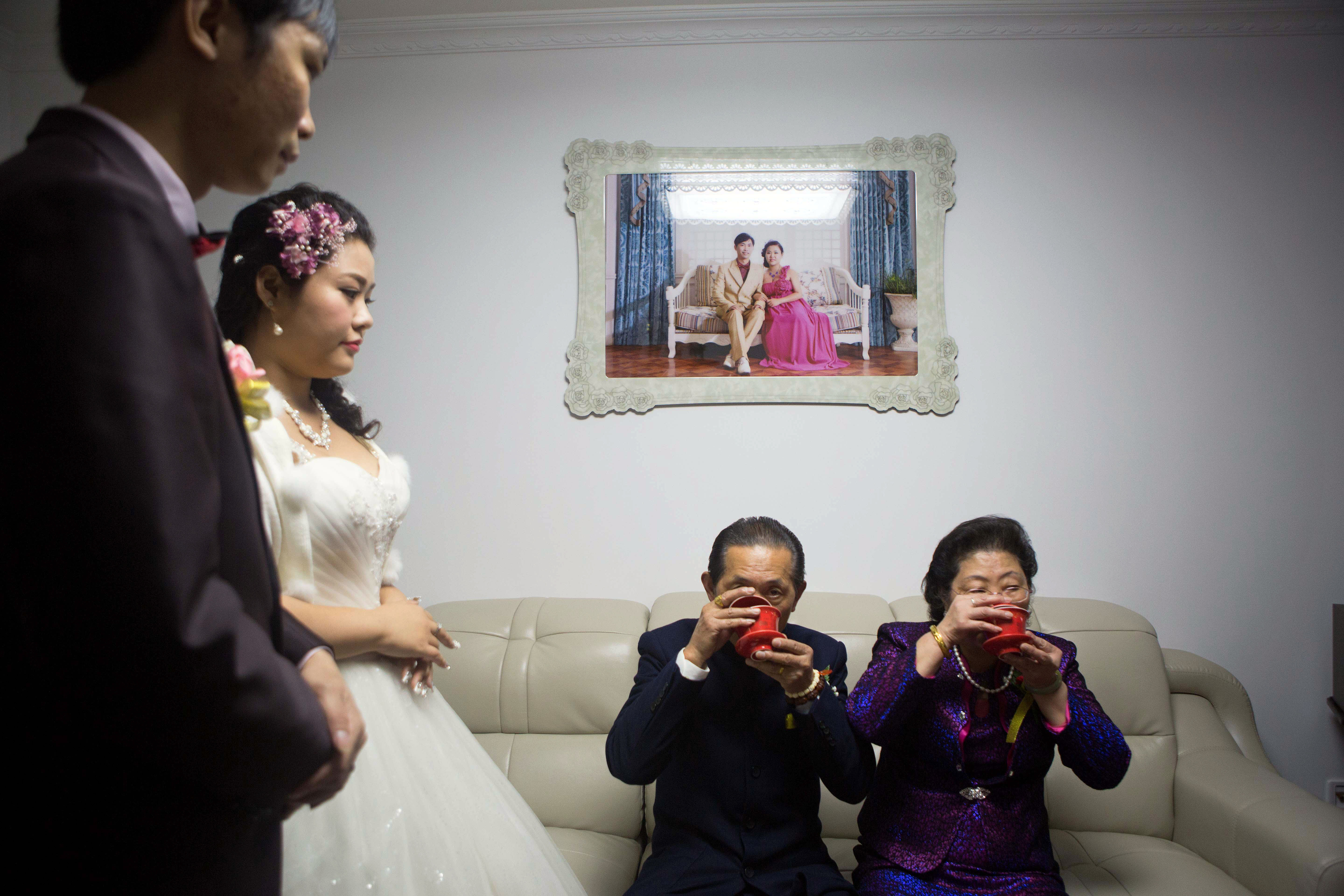 Xia Jiachen and Xu Chuyun, at left, honor the groom's grandparents during their wedding in December 2015. Pre-wedding photos are displayed on the wall.