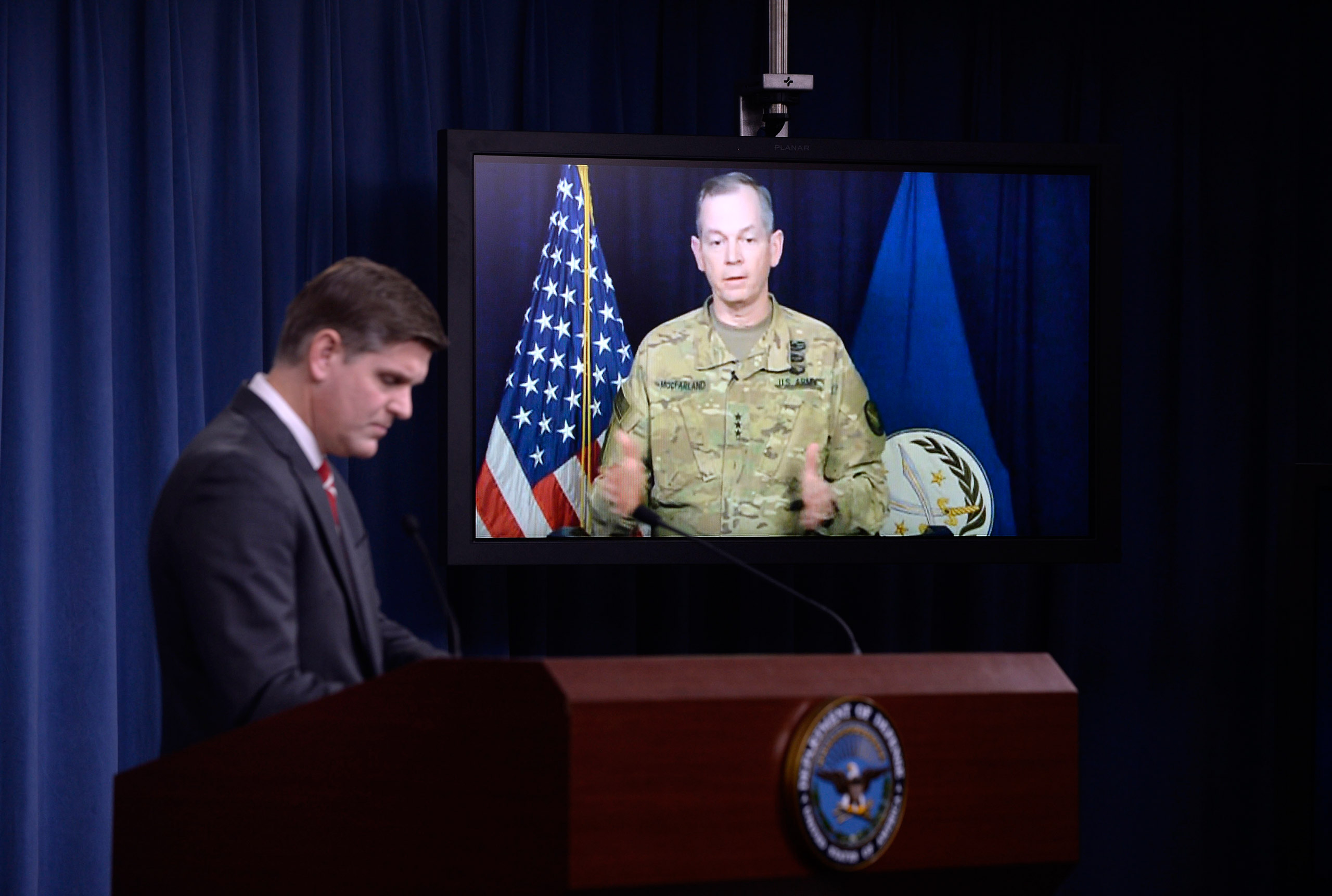 Commander Army Lt. Gen. Sean MacFarland speaks via teleconference from Baghdad, Iraq as Pentagon Press Secretary Peter Cook listens during a media briefing at the Pentagon in Arlington, Va., on Feb. 1, 2016.
