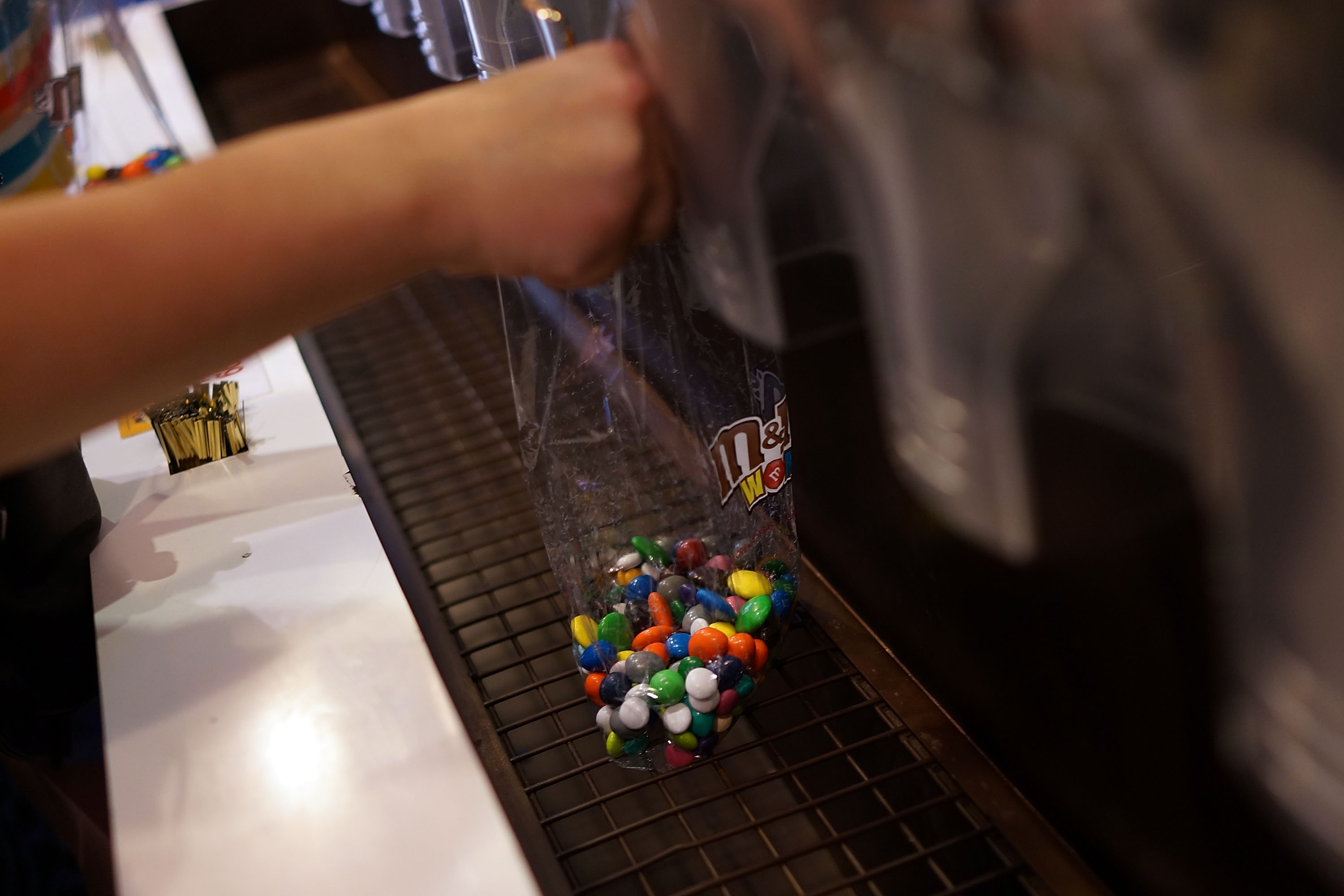 People fill up bags of M&M's at the M&M store in Times Square in New York City on July 24, 2014.