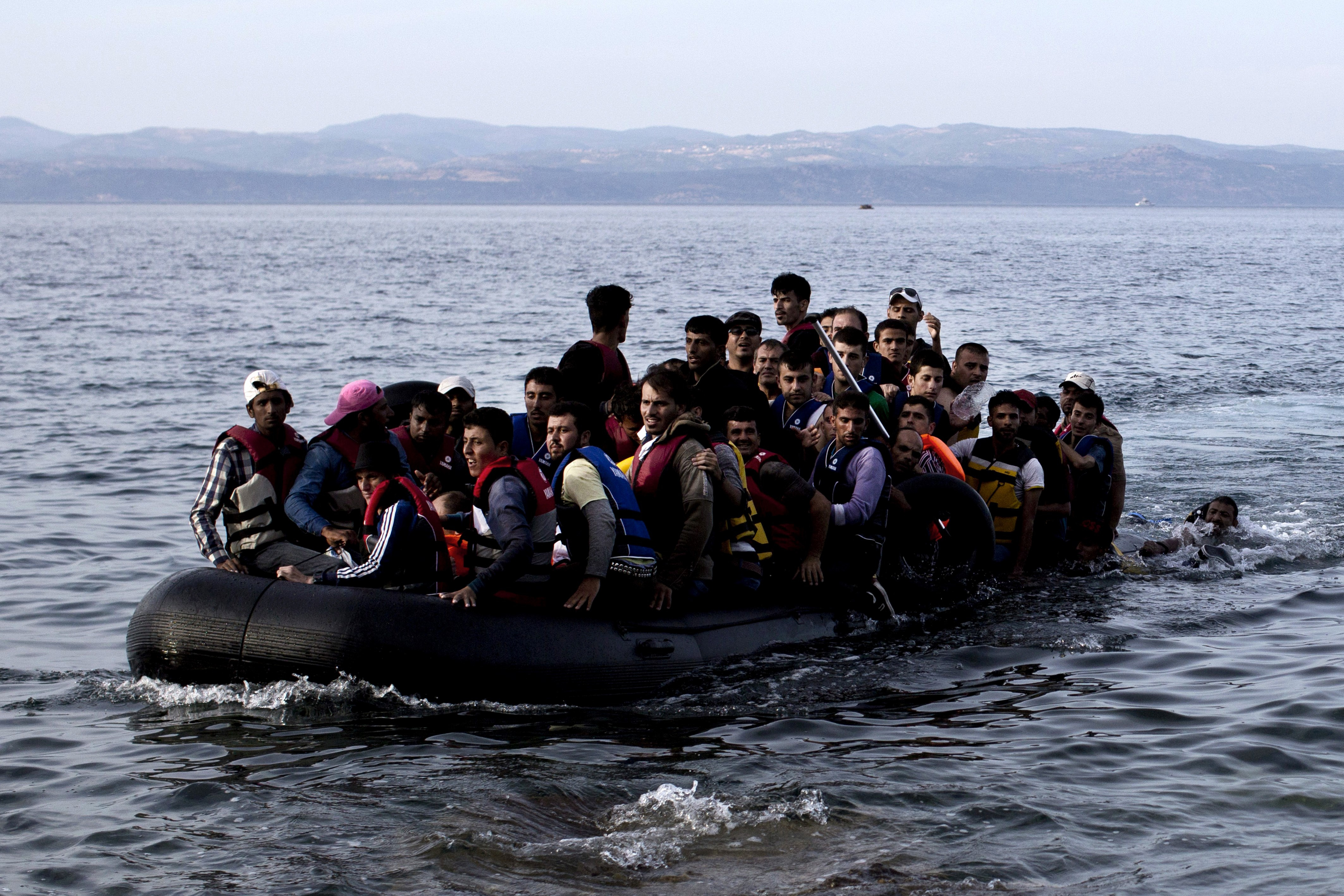 Refugees and migrants arrive on the shores of the Greek island of Lesbos after crossing the Aegean Sea from Turkey on an inflatable boat, Sept. 9, 2015.
