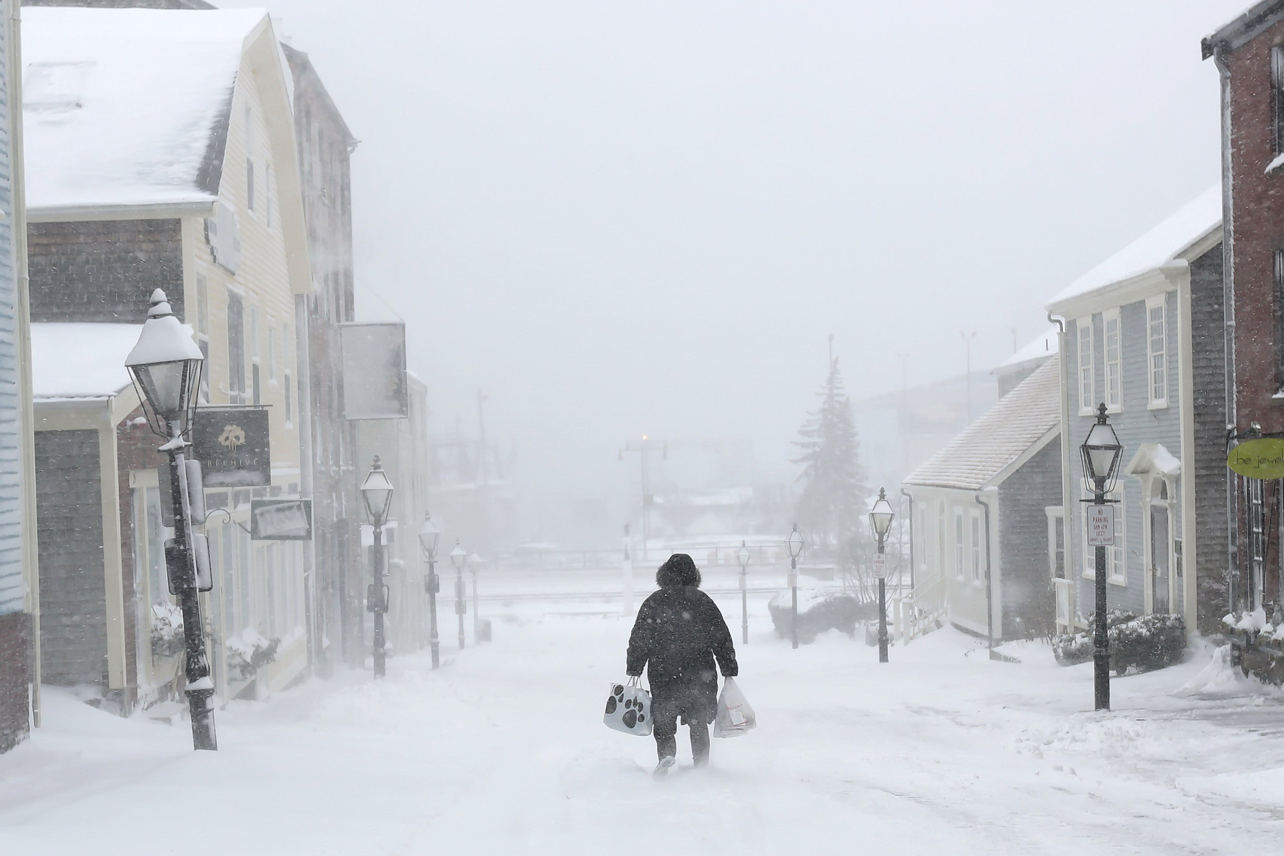 A woman walks down the street during a snowstorm in New Bedford, Mass., on Feb. 8, 2016.