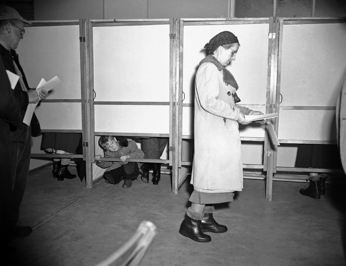 5-year-old Michael McNerney, tired of waiting for his mother to mark ballot in primary, peeps out below the door to the voting booth in Goffstown, N.H. on March 11, 1952.