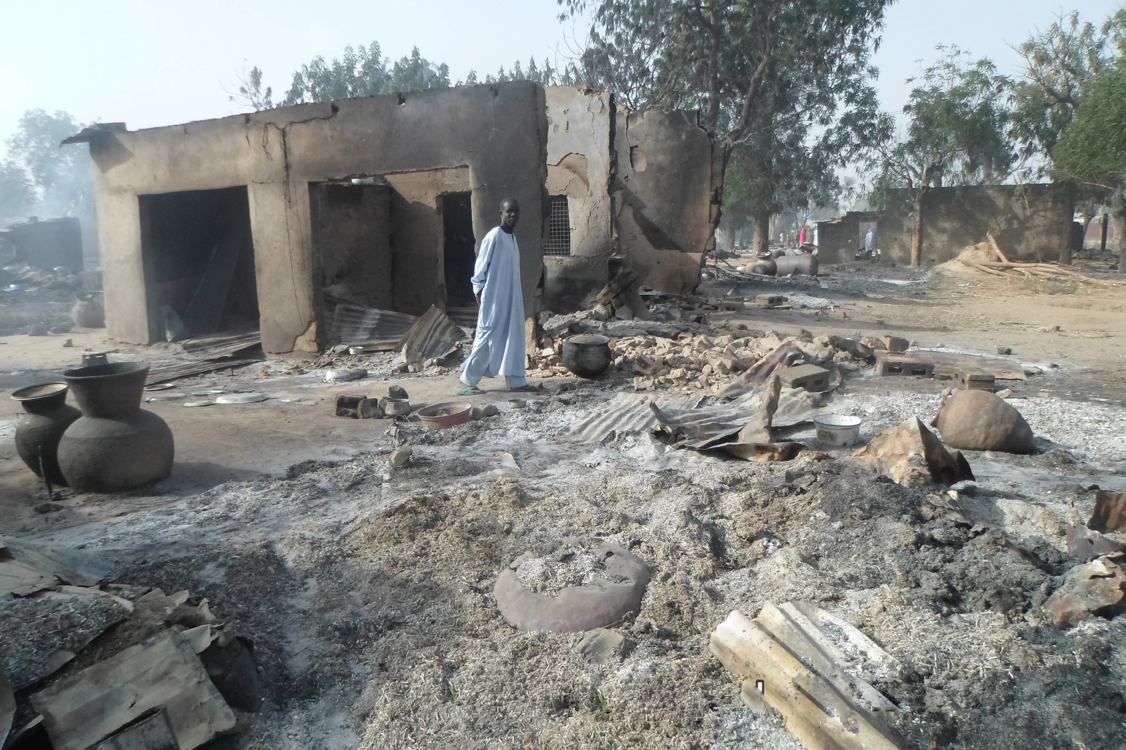 A man walks past burnt out houses following an attack by Boko Haram in the village of Dalori near Maiduguri, Nigeria, Jan. 31, 2016.