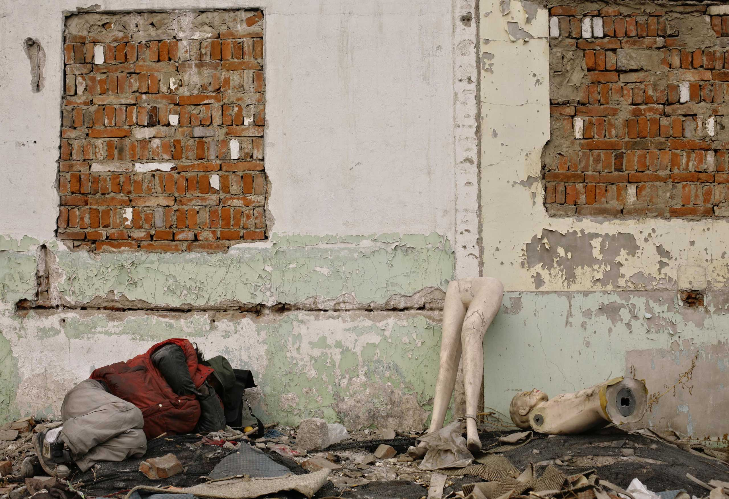 A man sleeps next to pieces of mannequins amongst the rubble of a demolished house in Beijing.