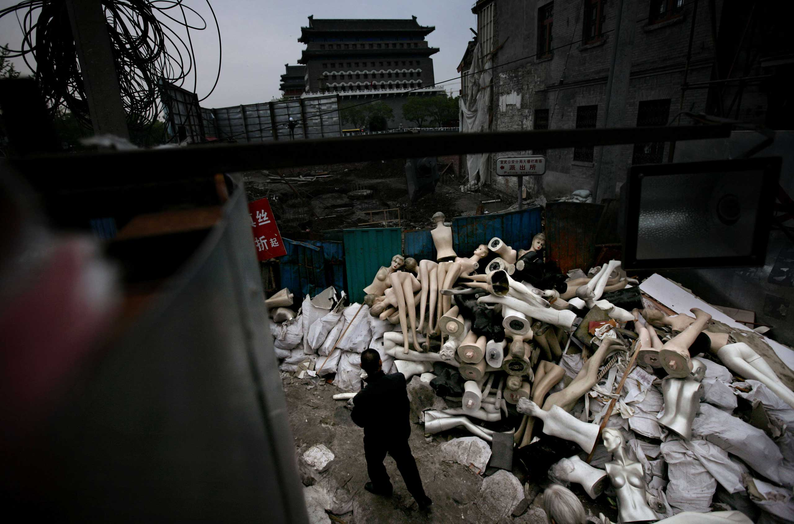 A Chinese man walks by mannequins amongst the rubble of demolished shops in Beijing.