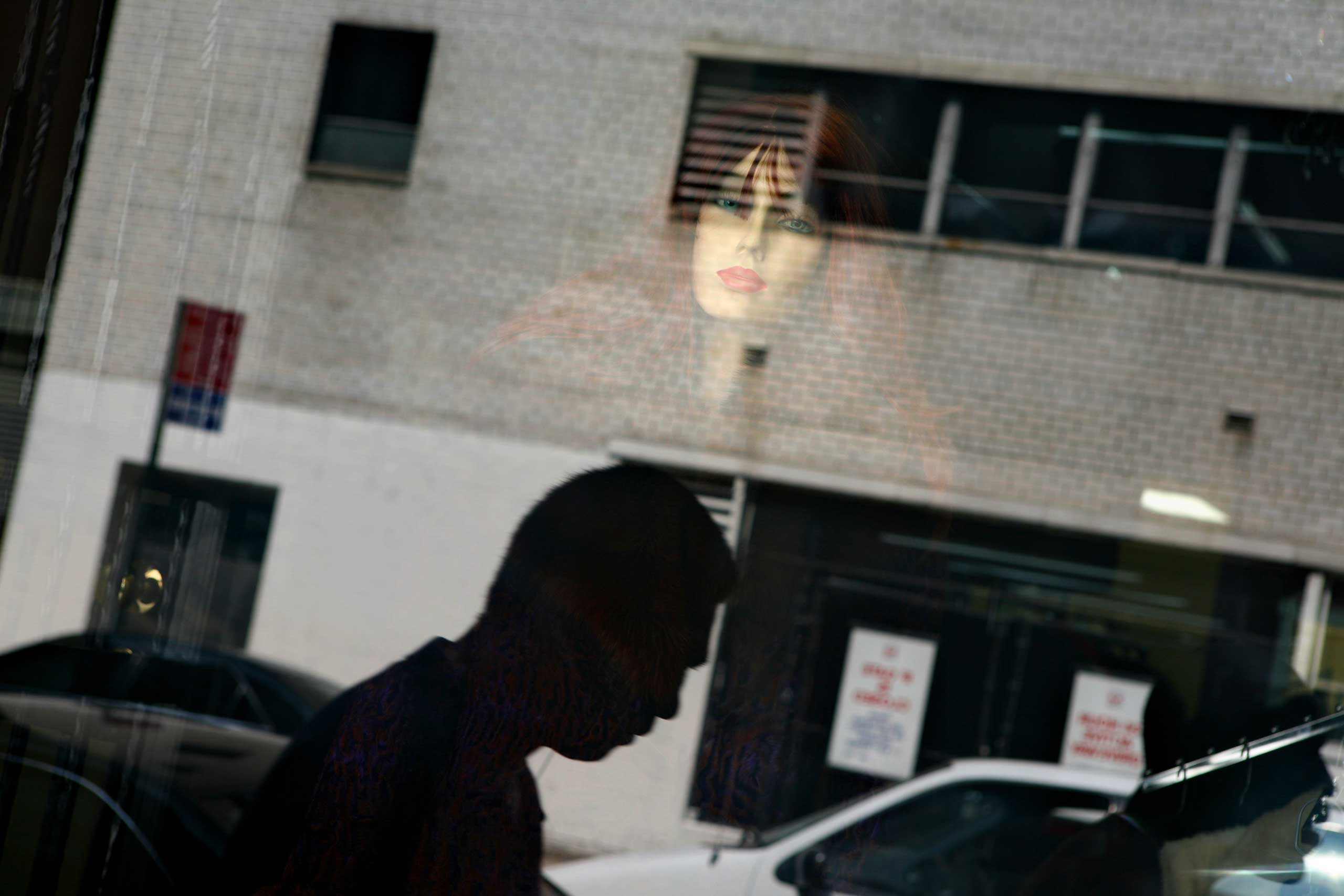 Mannequins and pedestrians are reflected in a clothing store window at the Fashion district during the Fashion Week.