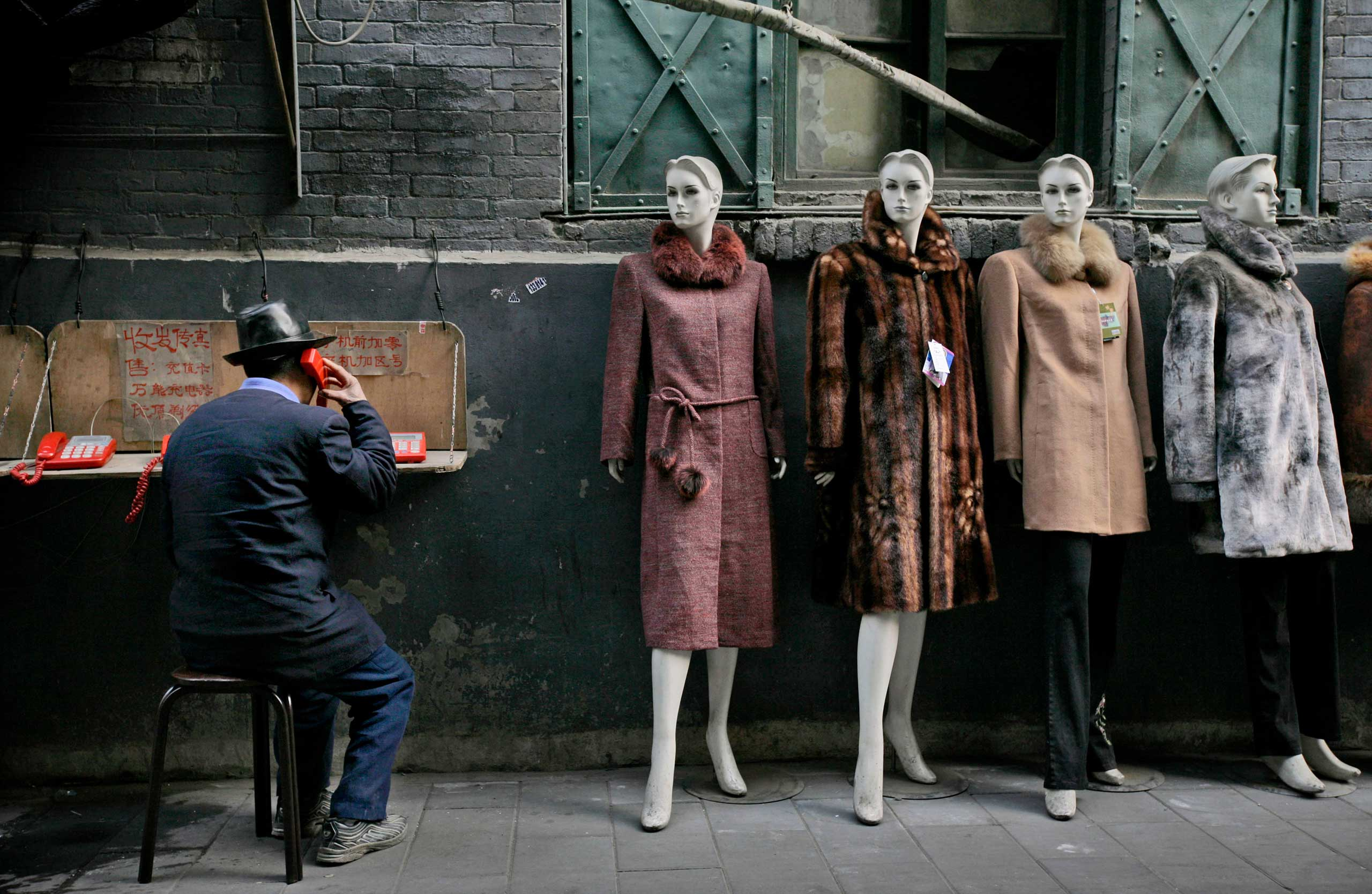 A man speaks on a pay phone next to a clothing shop at a market in Beijing.