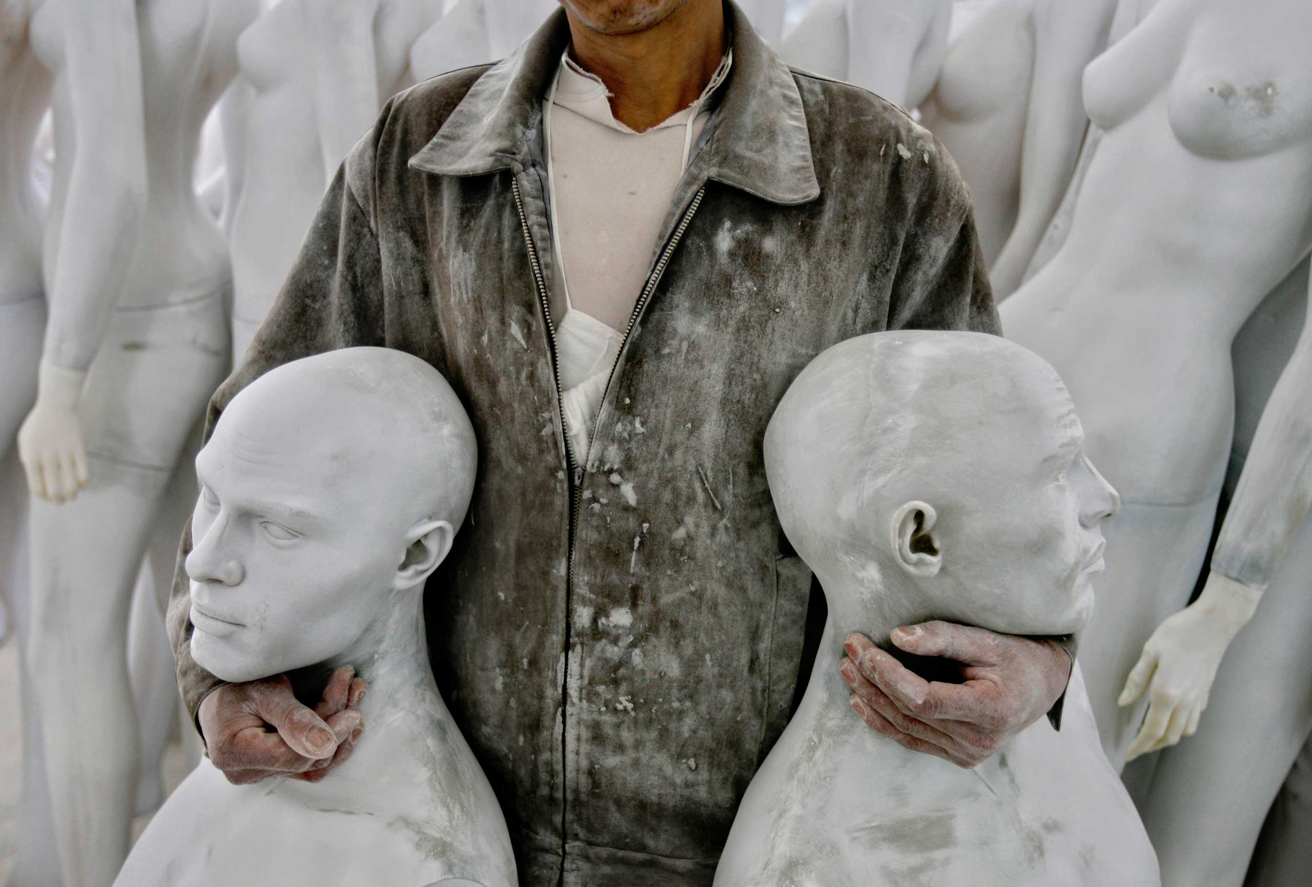 A Lucky Human mannequin factory employee holds mannequins, in the booming southern Chinese city of Shenzhen.