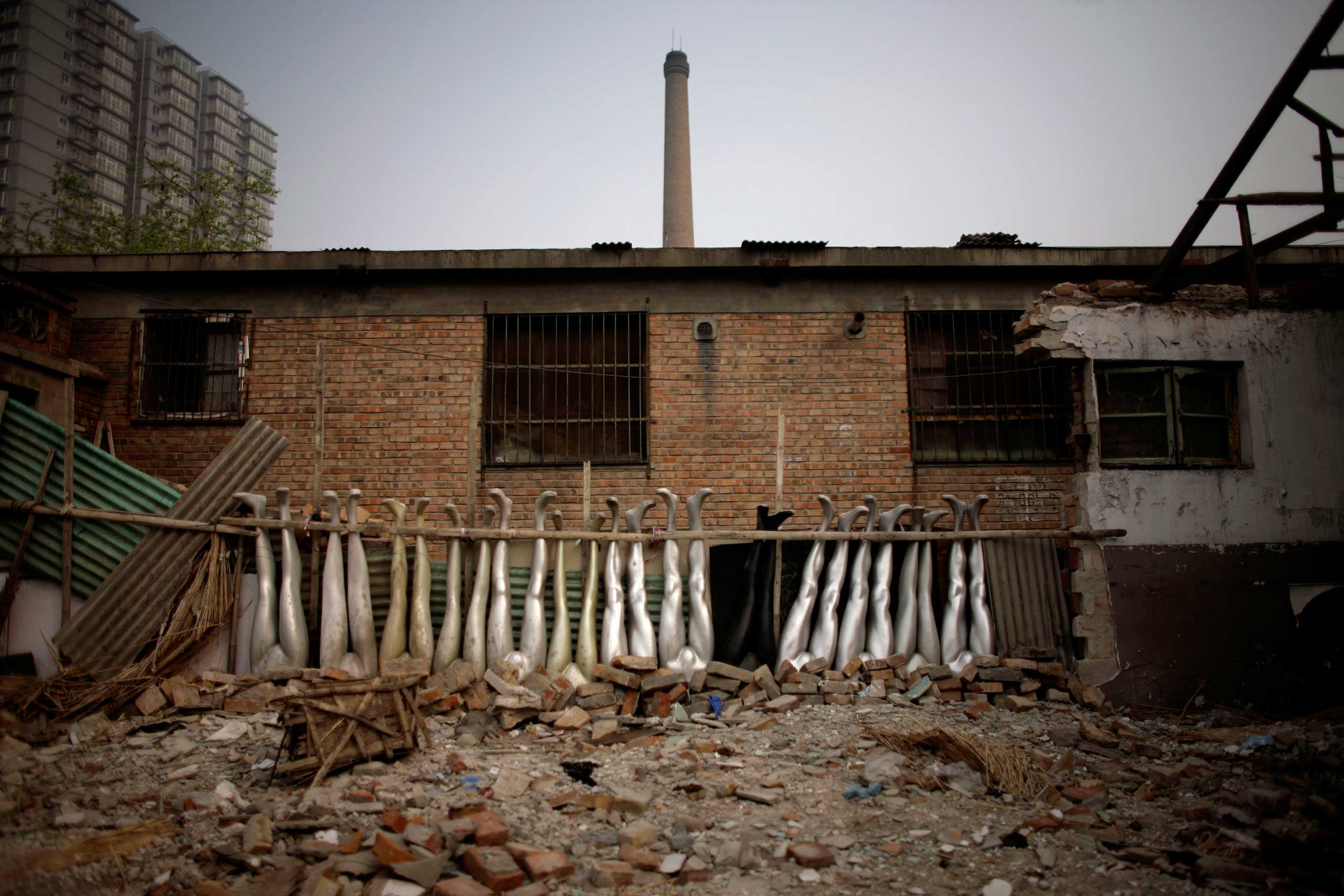 Mannequins legs lie amongst the rubble of a demolished house next to a construction site in Beijing.