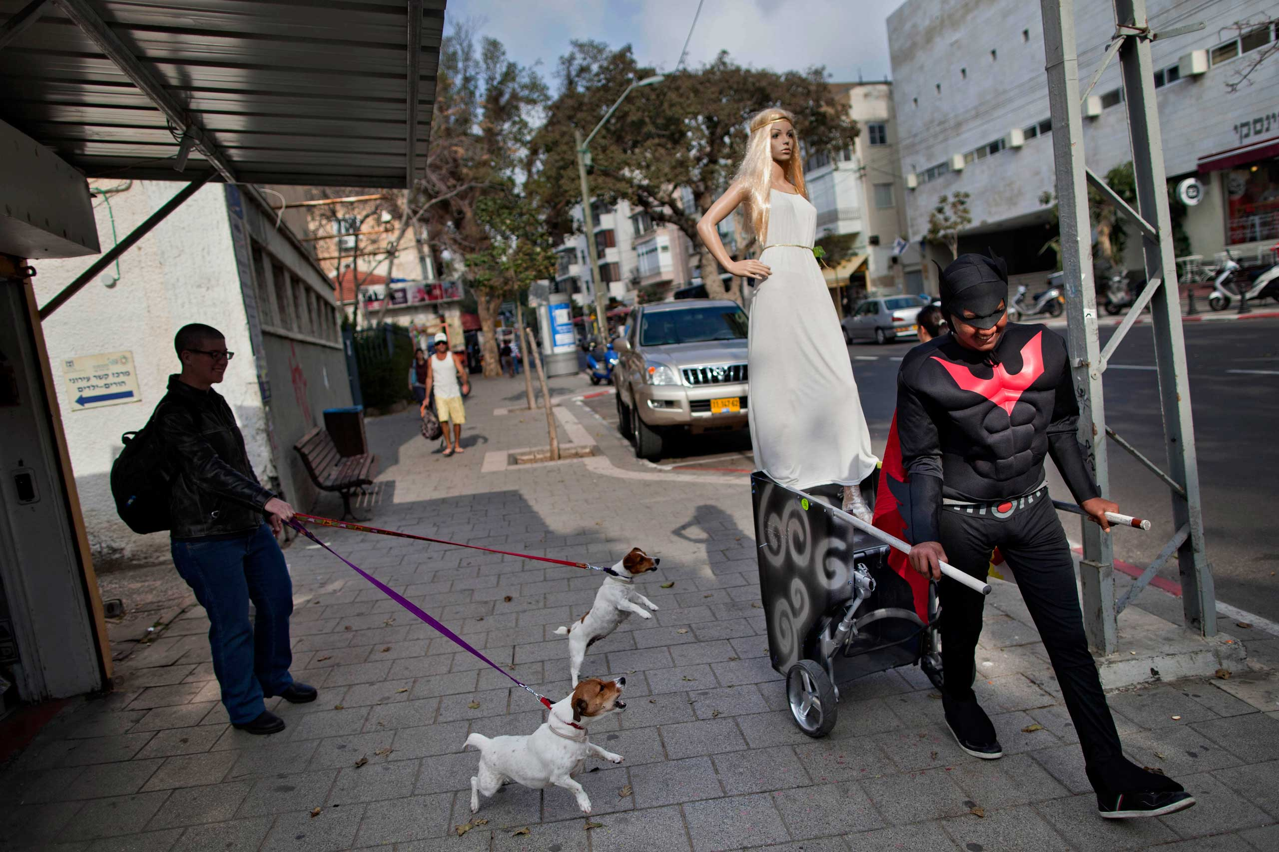 A costume shop employee, dressed as batman, pulls a cart with a mannequin to advertise the shop, ahead of the upcoming Jewish holiday of Purim, in Tel Aviv, Israel.
