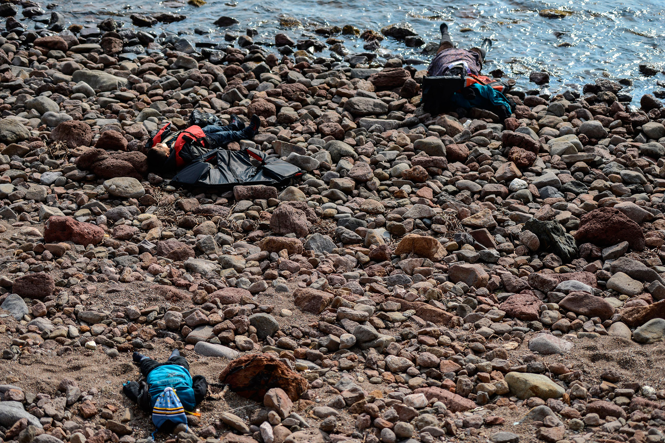 Three bodies are washed up on a beach after authorities said at least 37 people were killed when their boat capsized in the Aegean Sea while trying to cross to Greece from Canakkale province, Turkey, Jan. 30, 2016.