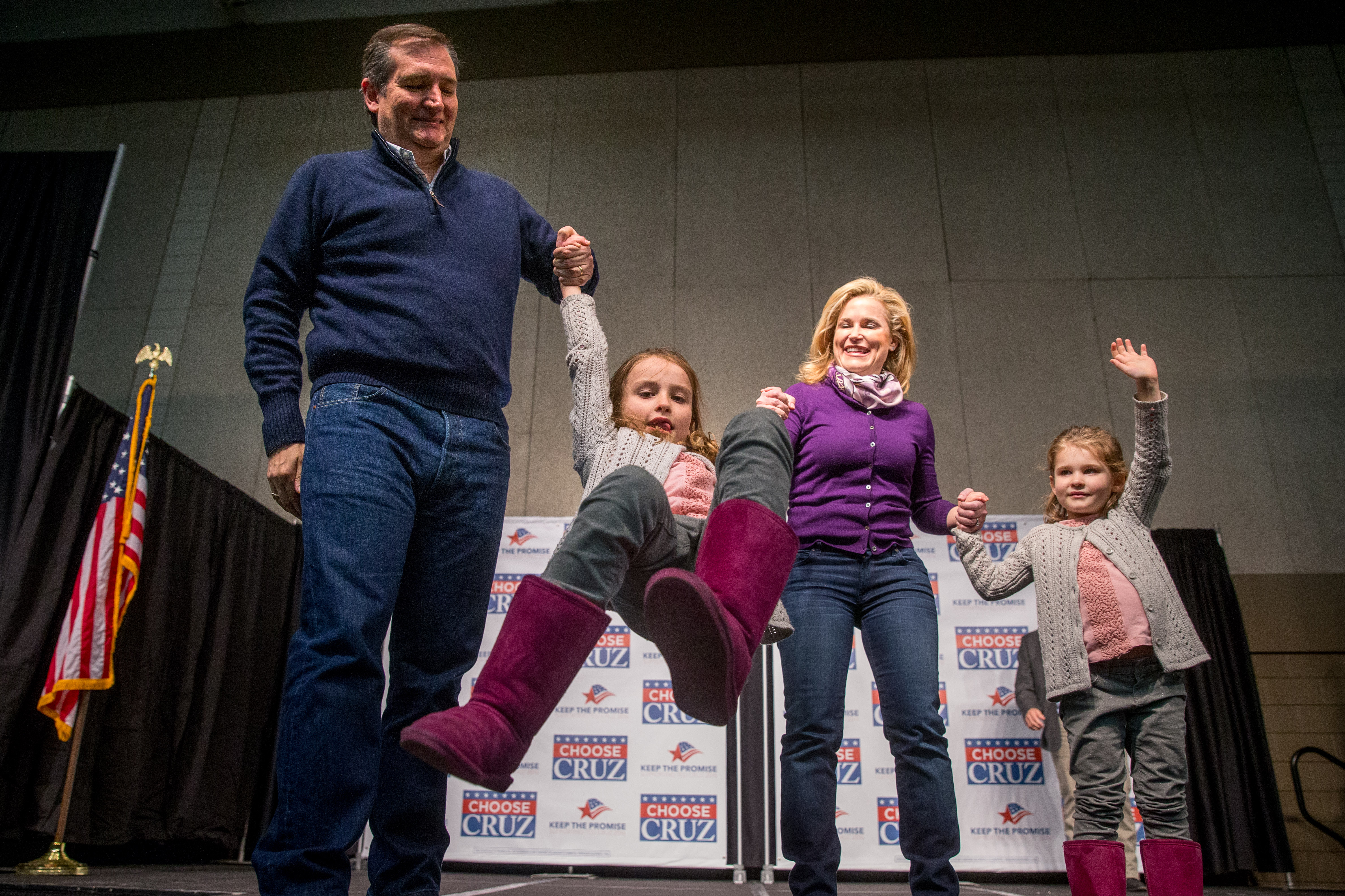 Republican presidential candidate, Texas Sen. Ted Cruz, and his wife Heidi swing their daughter Caroline, 7, as their daughter Catherine, 4, waves at a rally in Waterloo, Iowa, on Jan. 23, 2016.