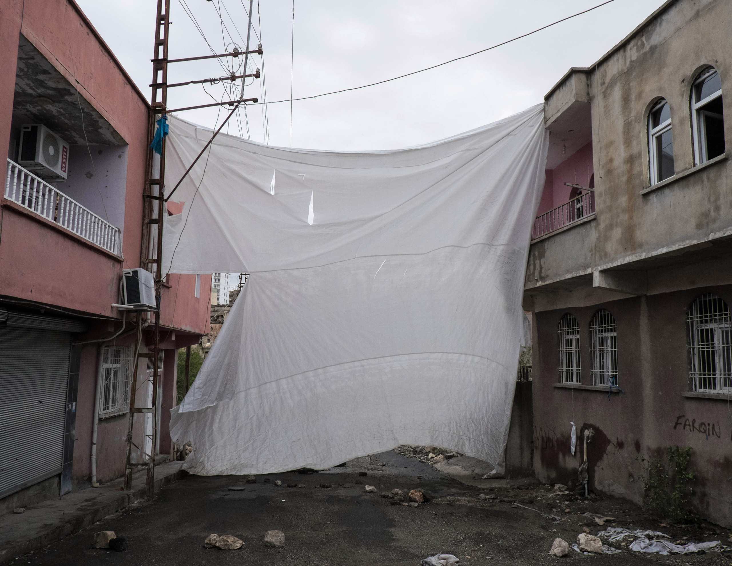 A veil covers an entrance in the Tekel neighborhood in Silvan, Turkey, on Oct. 27, 2015. Since July, the town of Silvan has been the theater of heavy clashes between Turkish military forces and Kurdish youth militias. A number of neighborhoods declared autonomy and self-rule;  groups of young Kurds under the acronyms of HPG (People Defense Union) and YDGH (Patriotic Revolutionary Youth Movement) have taken up arms and raised barricades to prevent the advances of the Turkish forces.