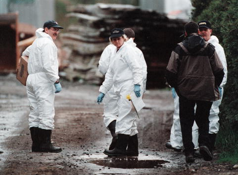 Investigators walk through the property owned by Dave and Robert William Pickton on April 17, 2002 in Port Coquitlam, British Columbia as part of a continuing investigation into women who disappeared from the Vancouver area over the past two decades.
