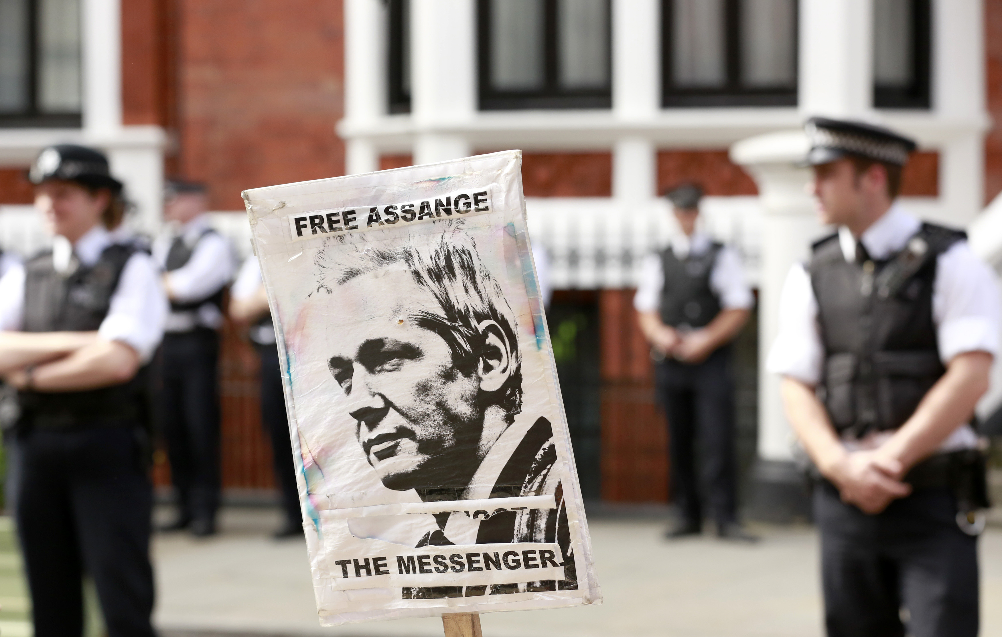Police and protesters wait for Wikileaks founder Julian Assange to speak to the media outside the Ecuador embassy in west London August 19, 2012.
