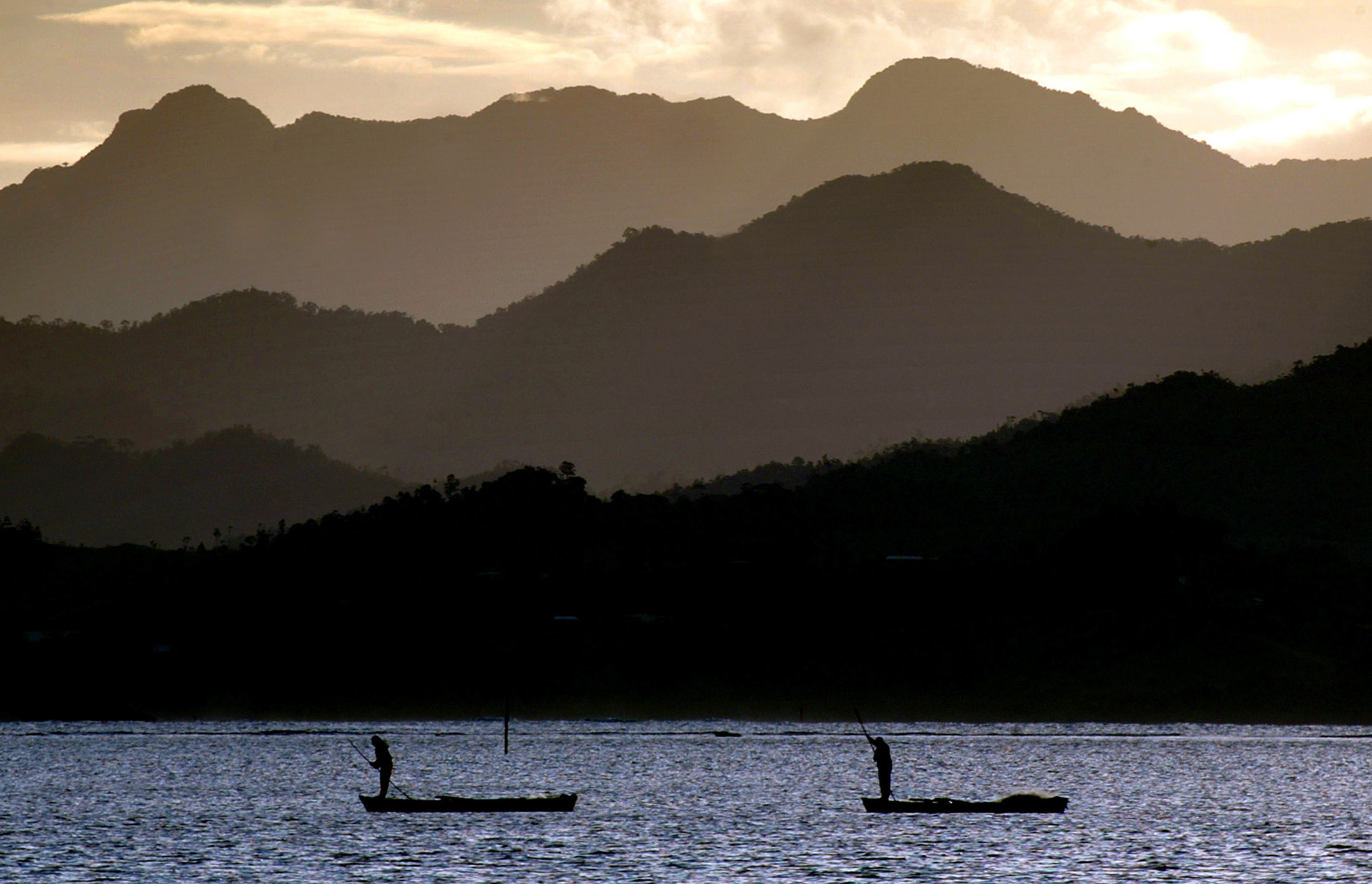 Fijian fishermen stand in their boats as they work in front of an island's mountain range near Suva April 29, 2004. C