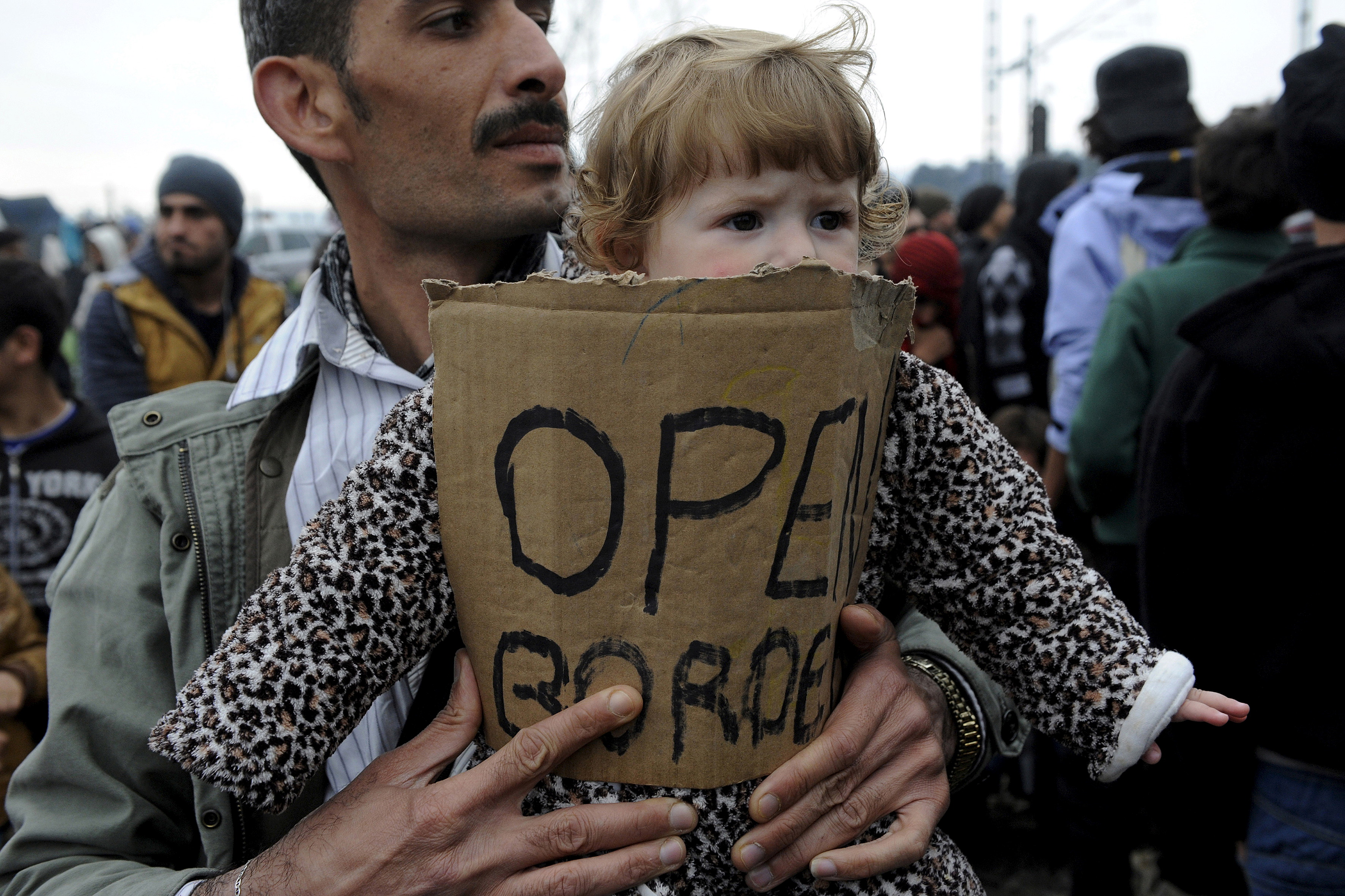 A stranded refugee holds a child during a protest at the Greek-Macedonian border, as they wait for the border crossing to reopen, near the Greek village of Idomeni on Feb. 28, 2016