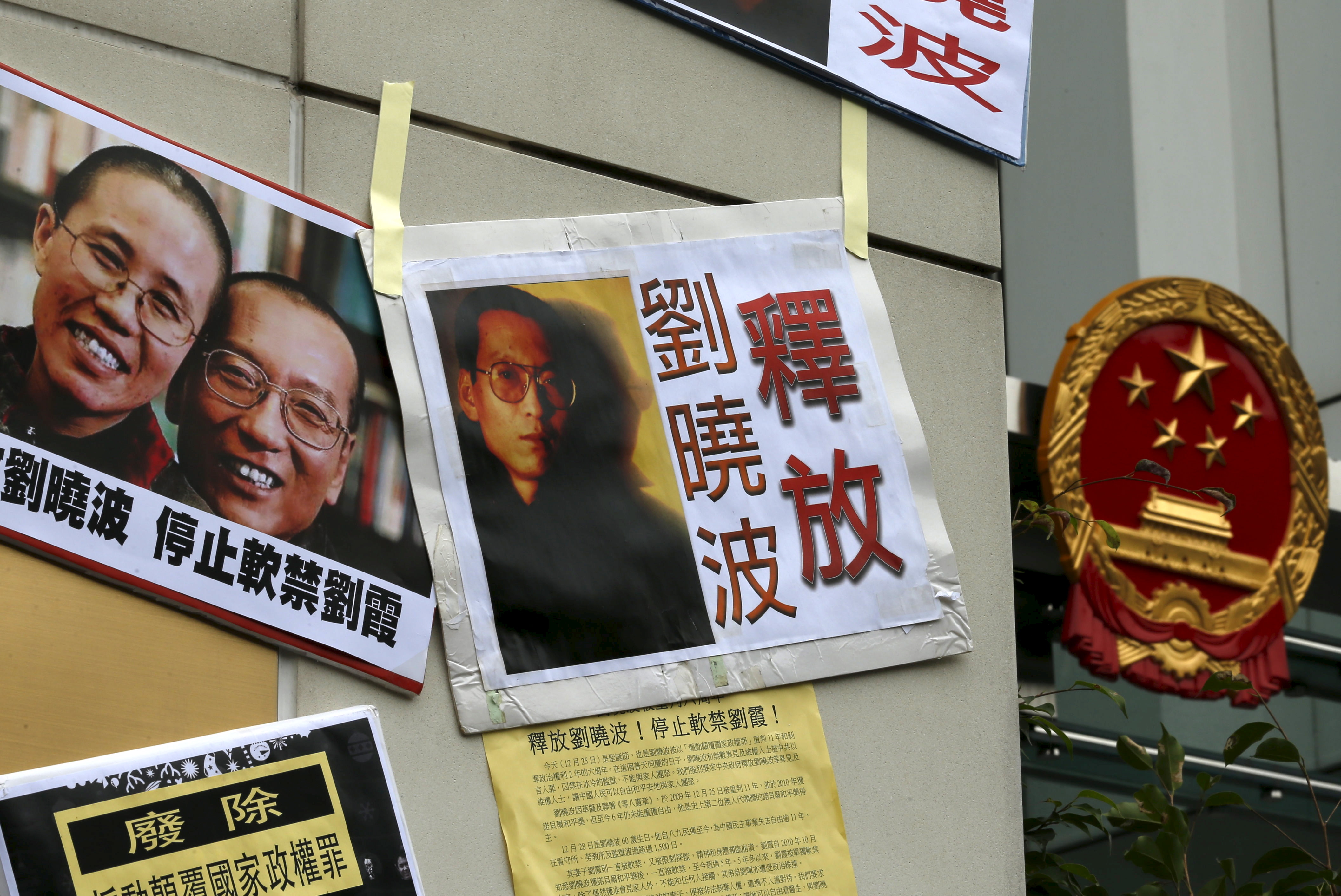 Signs and portraits of jailed Chinese Nobel Peace Prize laureate Liu Xiaobo and his wife Liu Xia during a protest outside the Chinese liaison office in Hong Kong on Dec. 25, 2015