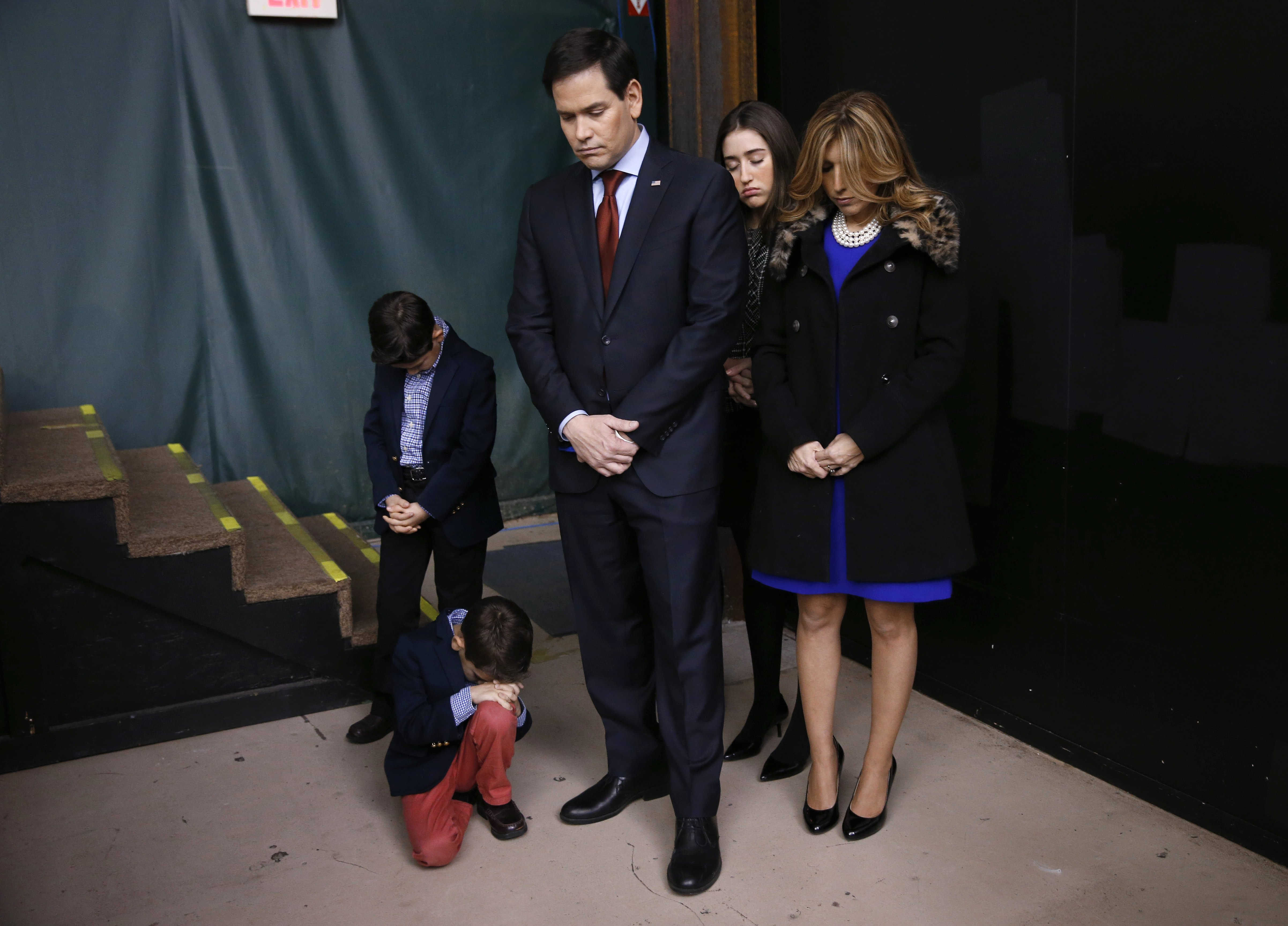 Republican presidential candidate Sen. Marco Rubio and his family pray during opening of a caucus site, Feb. 1, 2016 in Clive, Iowa.