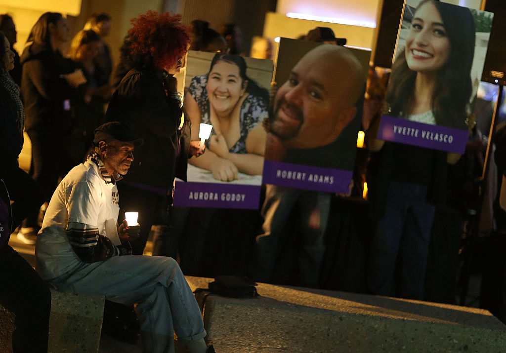 Photographs of victims of the San Bernardino shooting are seen as people hold candles while attending a vigil held to remember those injured and killed on Dec. 7, 2015.