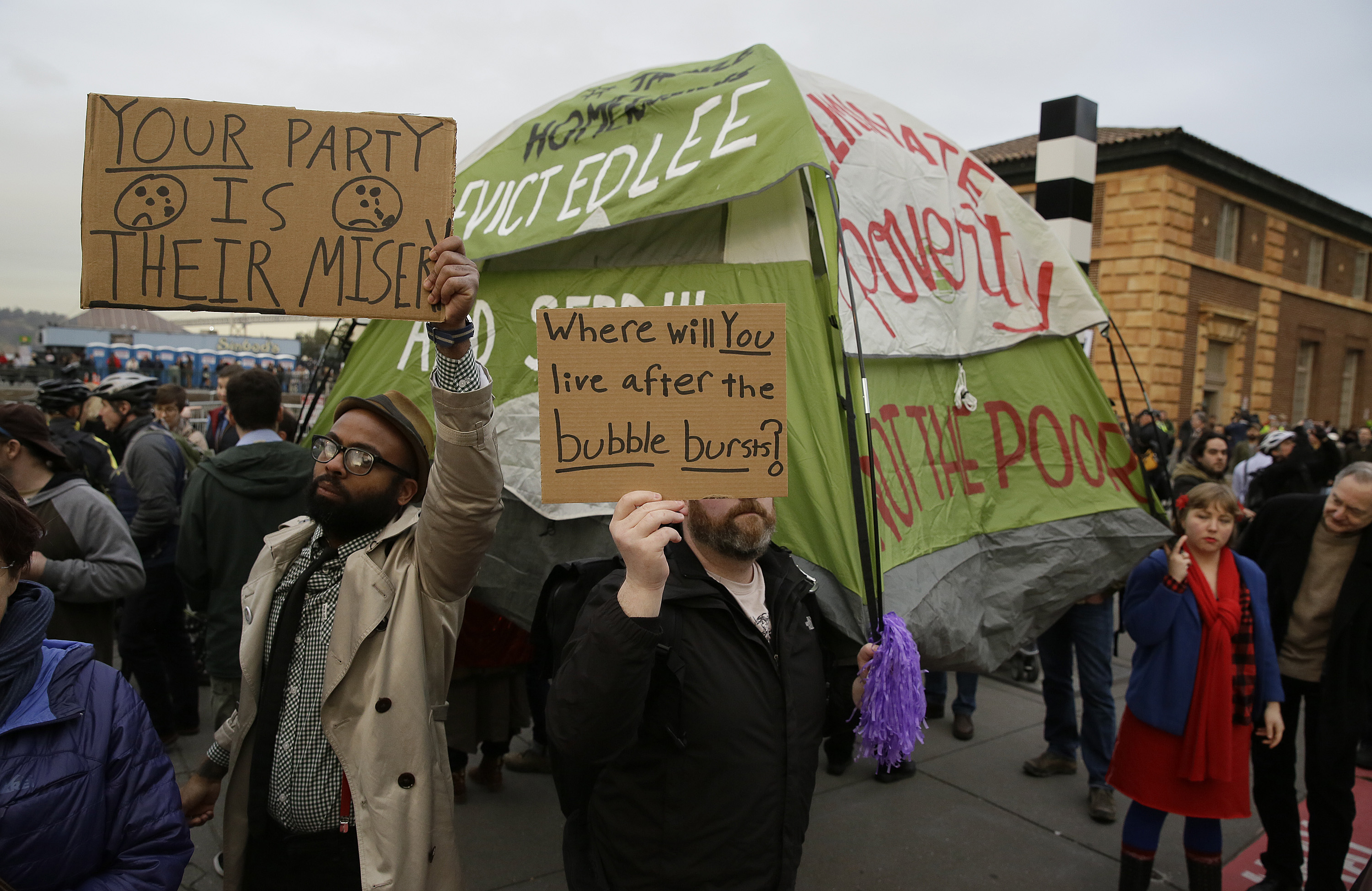 People hold up signs and a tent during a protest to demand city officials do more to help homeless people outside Super Bowl City, in San Francisco on Feb. 3, 2016.