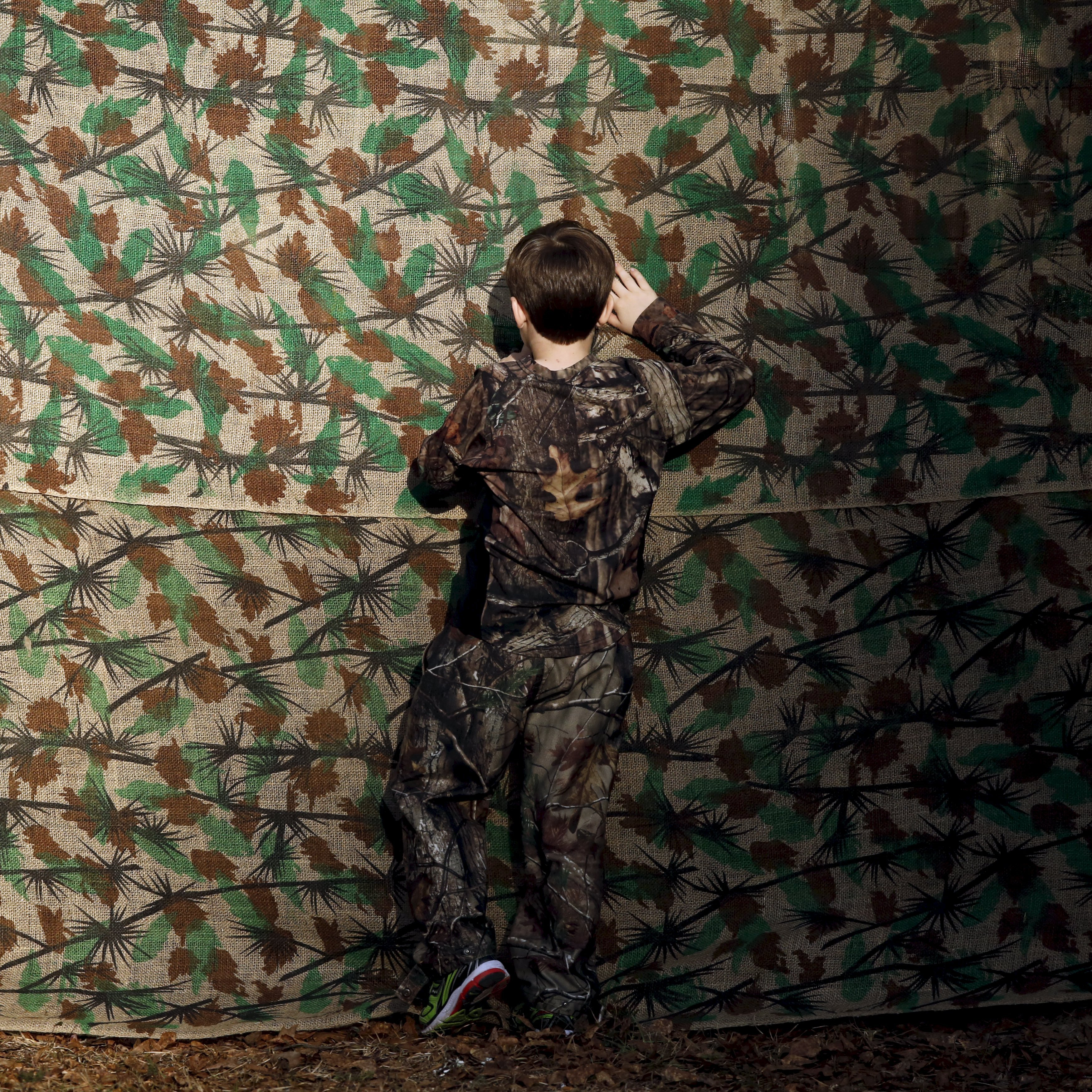 A young boy in camouflage clothing looks through a cloth backdrop to get a glimpse of U.S. Republican presidential candidate Donald Trump at a rally in Walterboro, S.C. on Feb. 17, 2016.