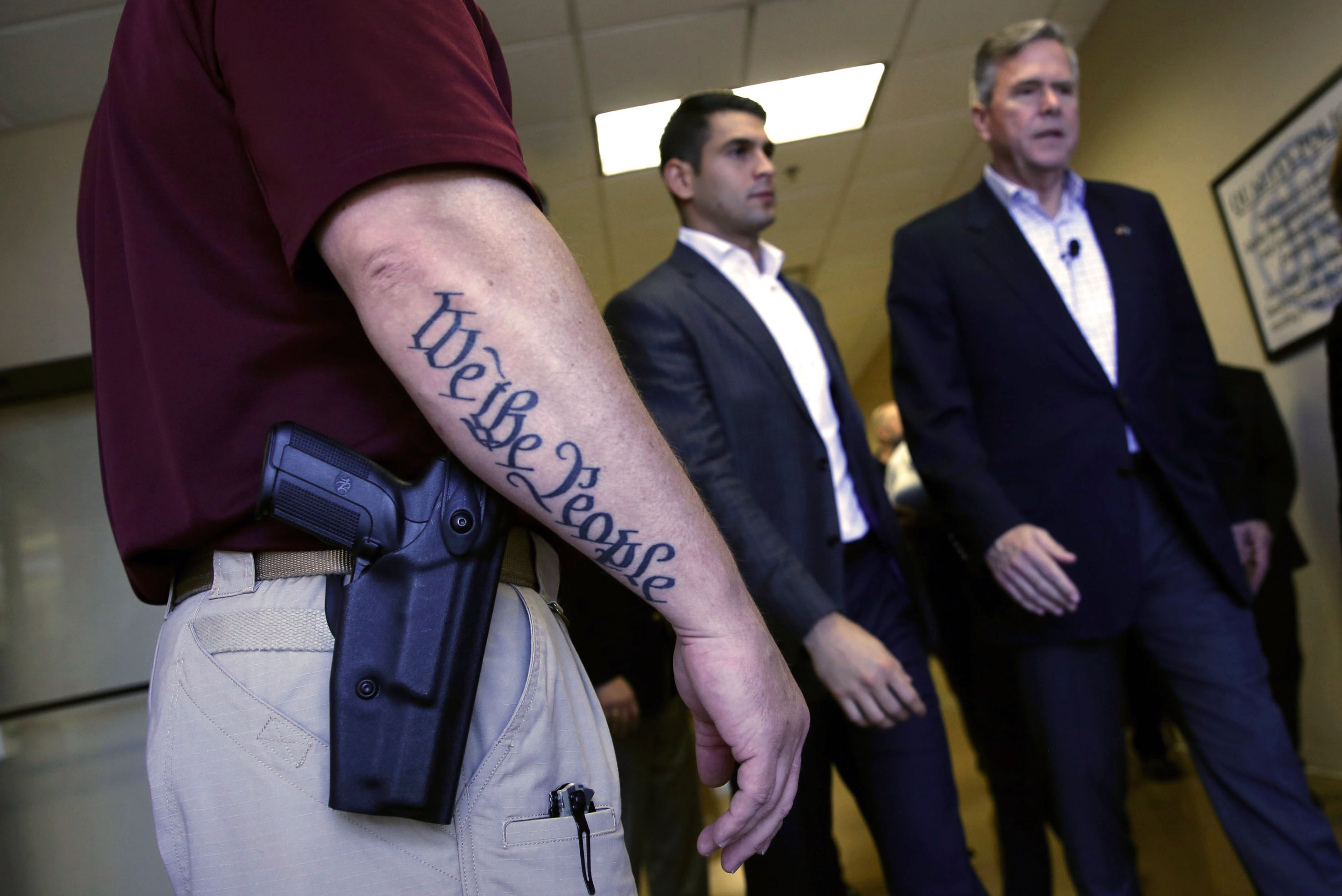 Republican presidential candidate Jeb Bush walks past a security guard after a town hall meeting with employees at FN America gun manufacturers in Columbia, S.C. on Feb. 16, 2016.