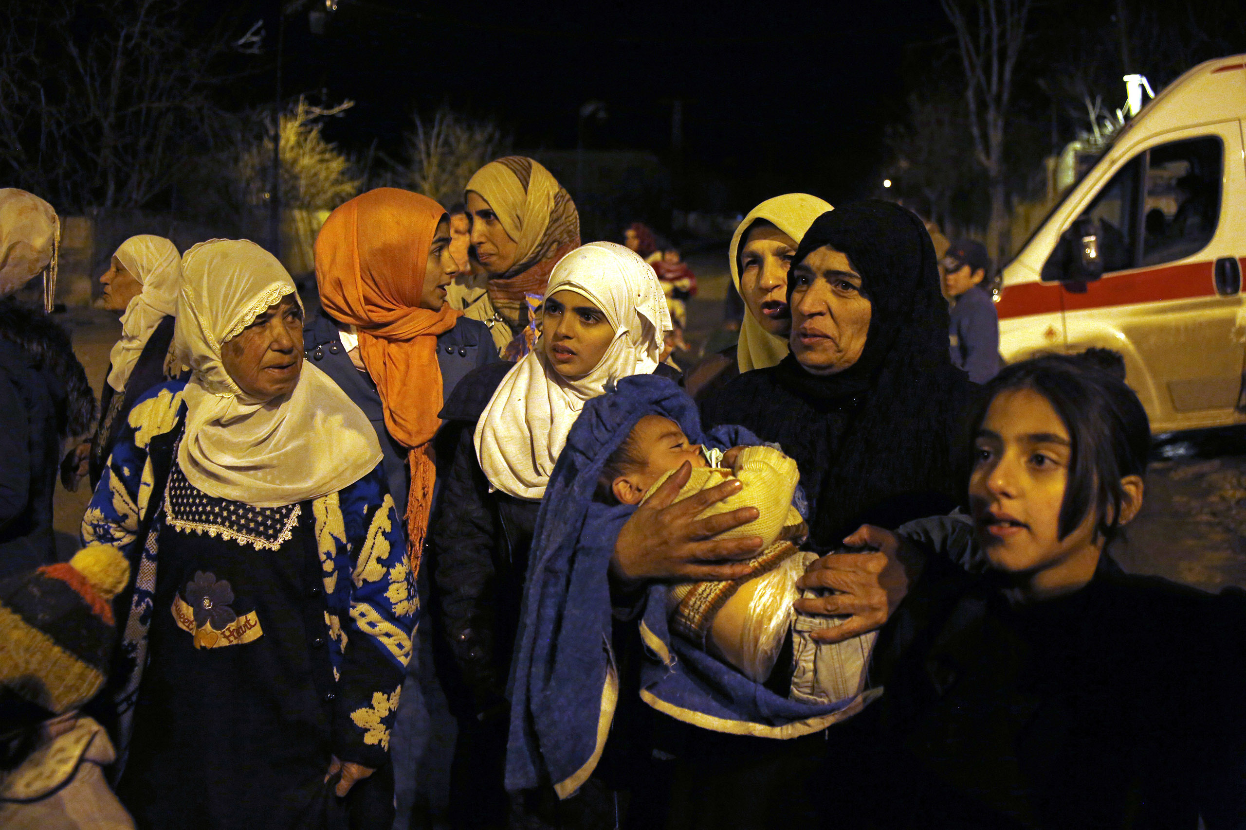 In this Jan. 11, 2016, photo, a group of women and young children wait to leave the besieged town of Madaya, northwest of Damascus, Syria. Doctors Without Borders says dozens of people in Madaya have died of starvation since September.