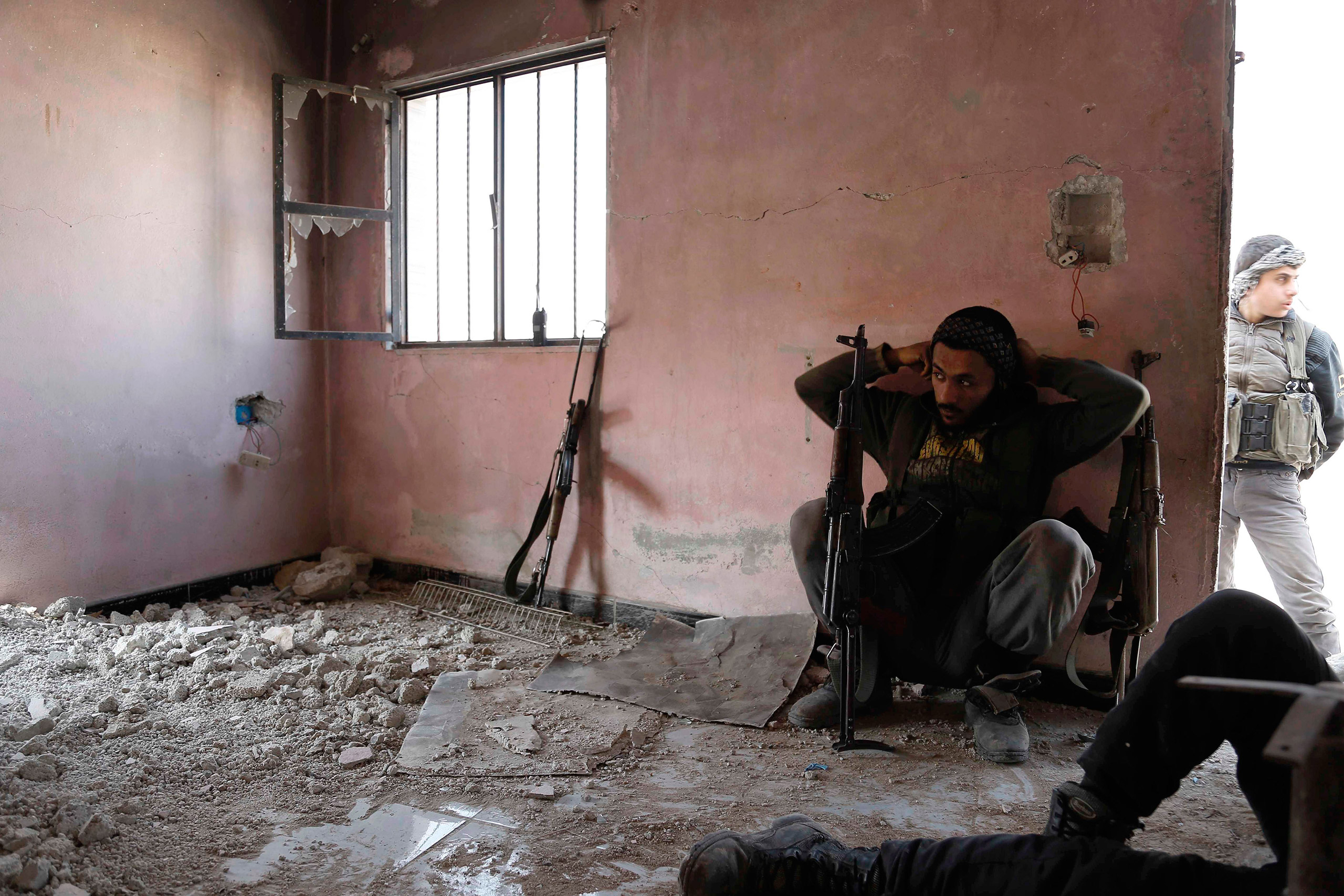Rebel fighters from the Failaq al-Rahman brigade take a break as they hide inside a building on the frontline against regime forces in the rebel-controlled village of Bala, on the outskirts of Damascus, Syria, Feb. 28, 2016.