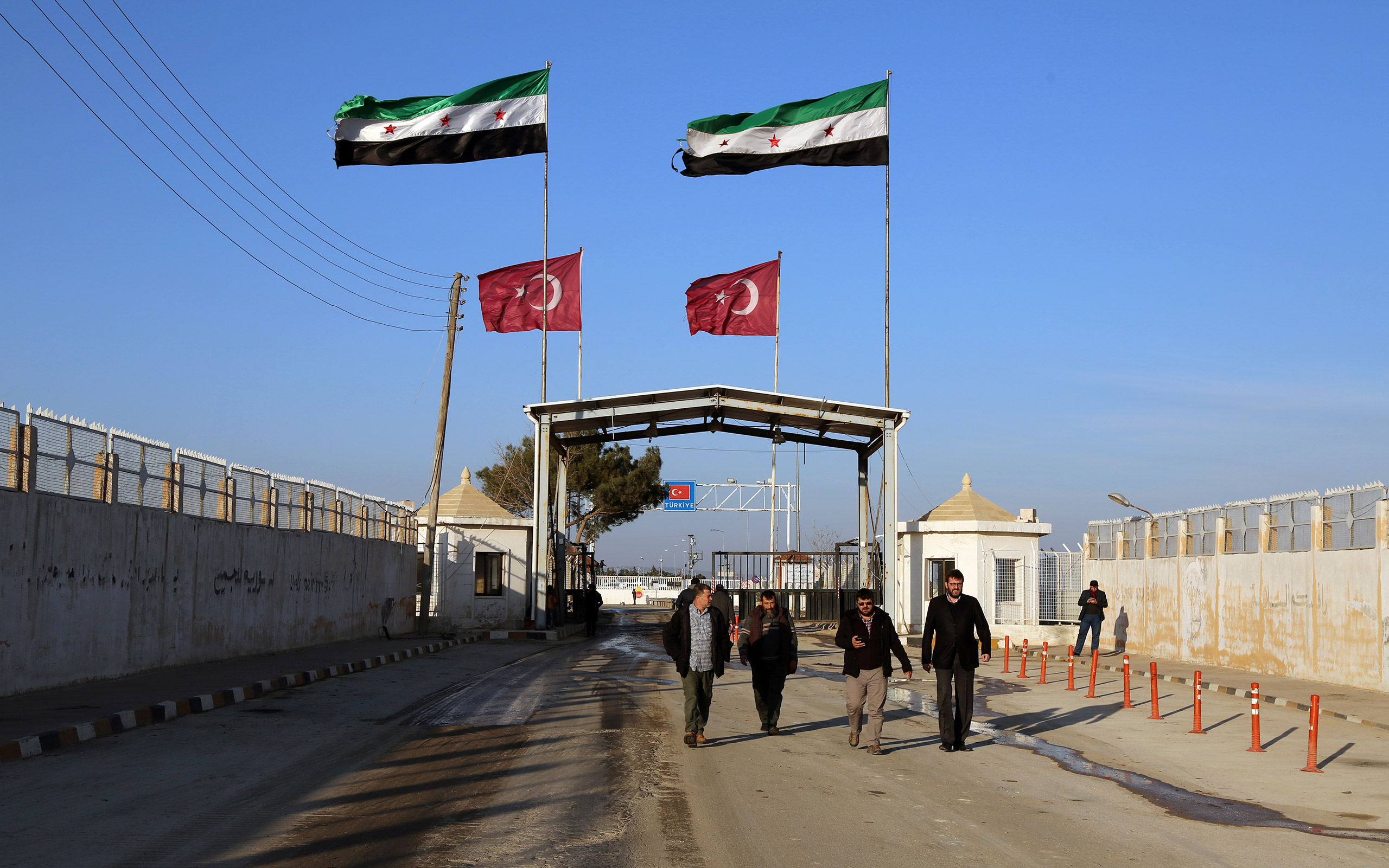 In this photo provided by Turkey's Islamic aid group of IHH, Syrians fleeing the conflict in Azaz region walk at the Bab al-Salam border gate, Syria, Feb. 5, 2016.