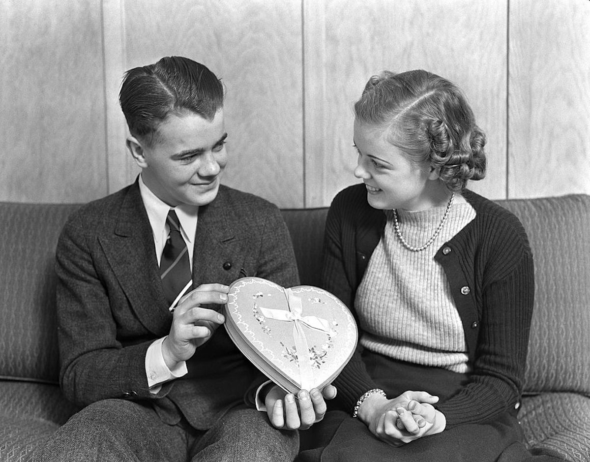 Circa 1930s:  smiling teen couple sitting on a sofa
