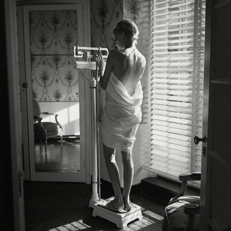 Woman weighing herself beside window in 1948