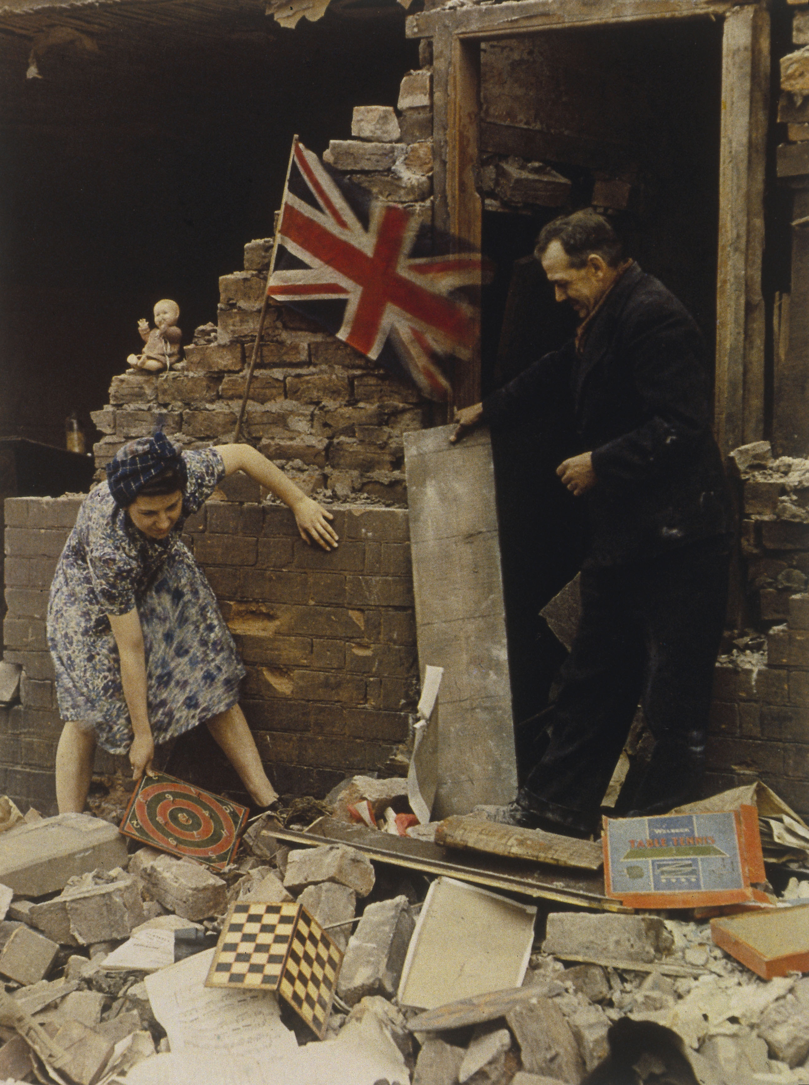 Woman saving board games from bomb wreckage, London, 1939-1945.