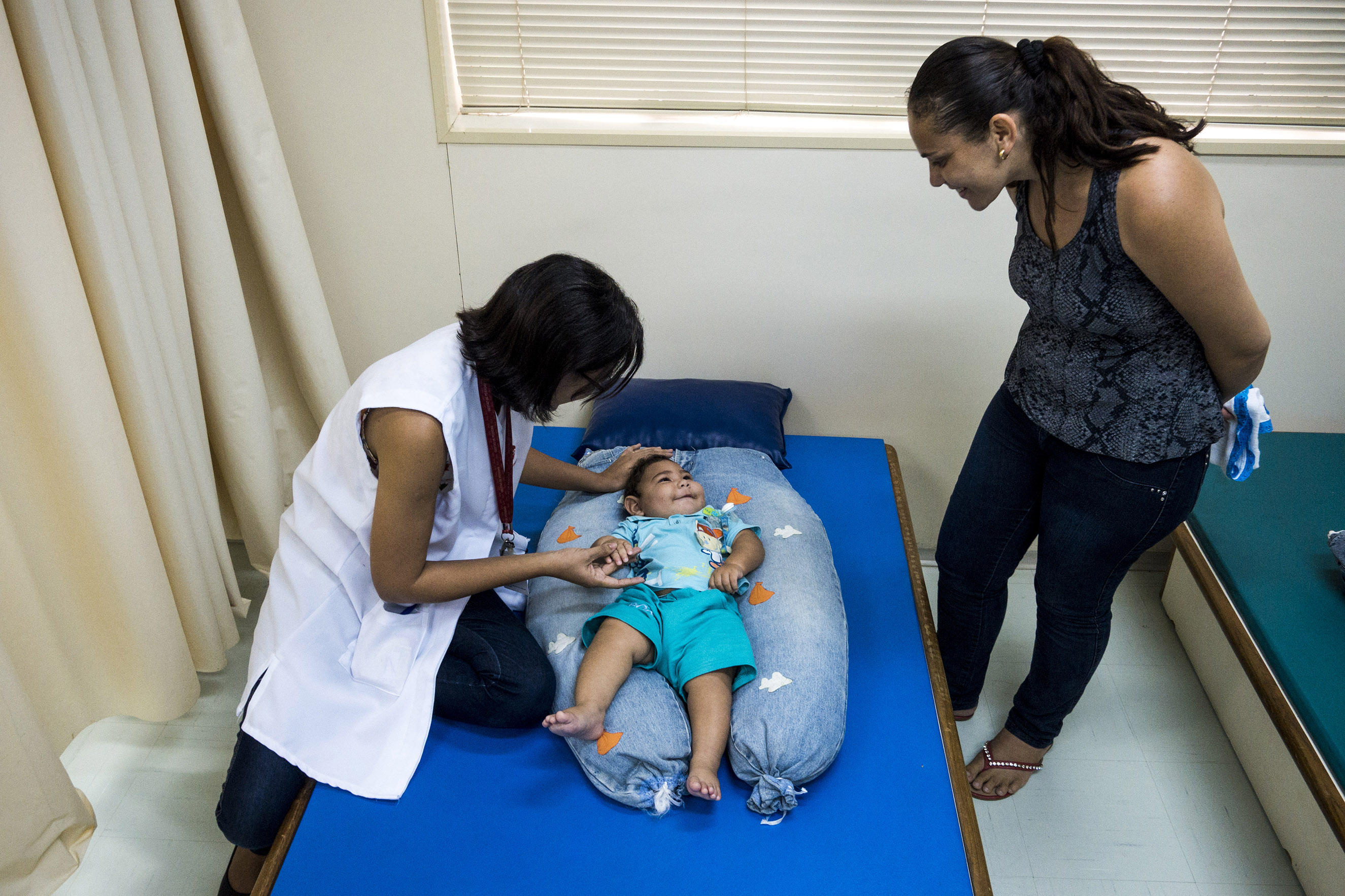 Dr. Cynthia de Melo Silva Ximenes, a physical therapist, works with Adriana Cordeiro da Silva, 29, and her 7-month-year-old son Jose Bernardo at the Associacao de Assistencia a Crianca Deficiente rehabilitation center in Recife, Brazil, Feb. 1, 2016. She drove five hours from Custódia for care.
