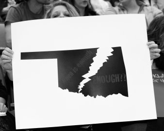 An attendee holds a protest sign at a public forum event hosted at the Univ. of Central Oklahoma, Edmond, OK