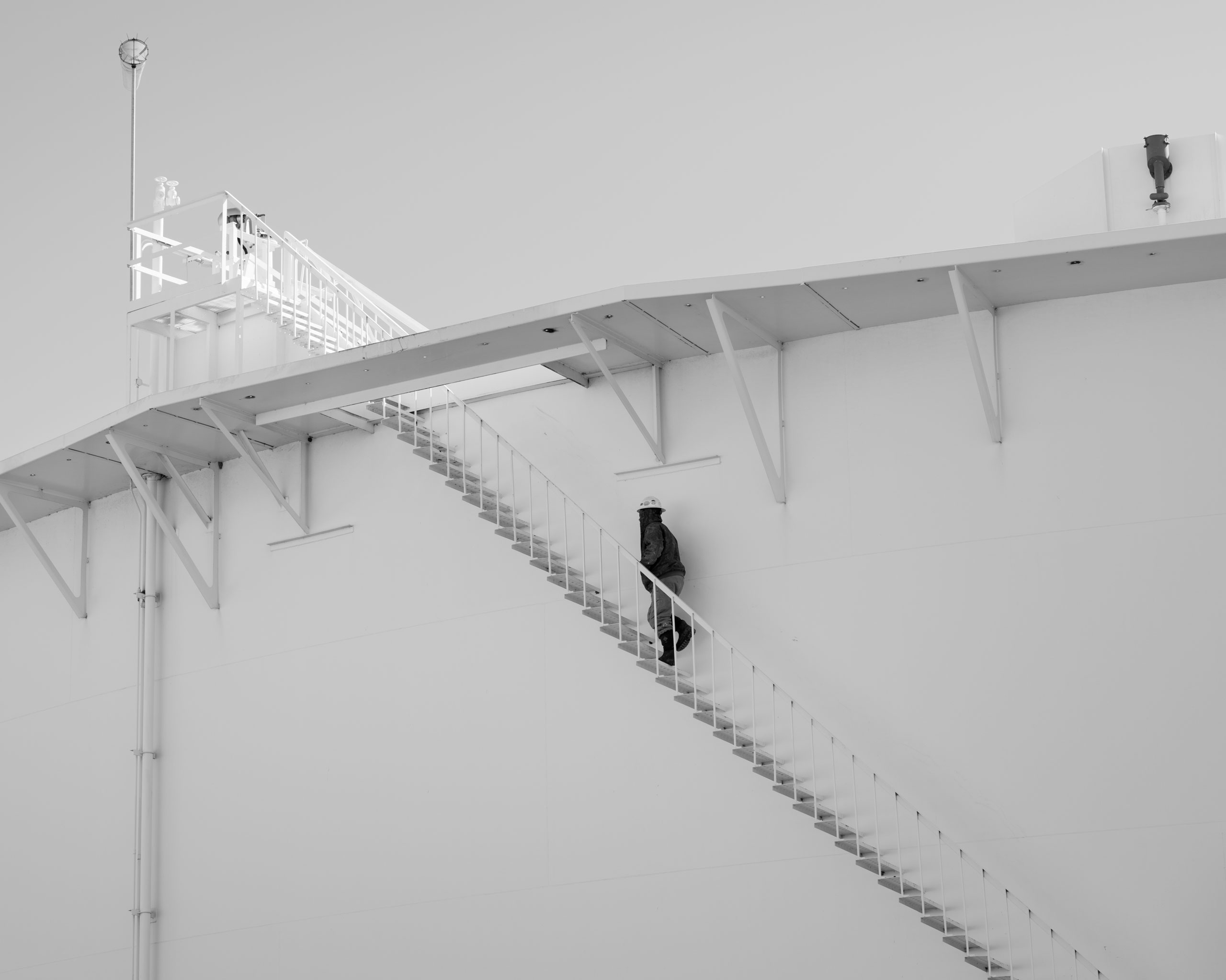 A worker walks up stairs on an oil storage tank, Cushing, Oklahoma. Cushing is a vital transshipment point with many intersecting pipelines, storage facilities and easy access to refiners and suppliers. Crude oil flows inbound to Cushing from all directions and outbound through dozens of pipelines. It is one of the largest oil reserves in the world.
