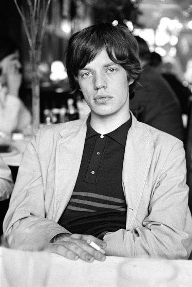 Rolling Stones singer Mick Jagger having a cigarette backstage; 1964.