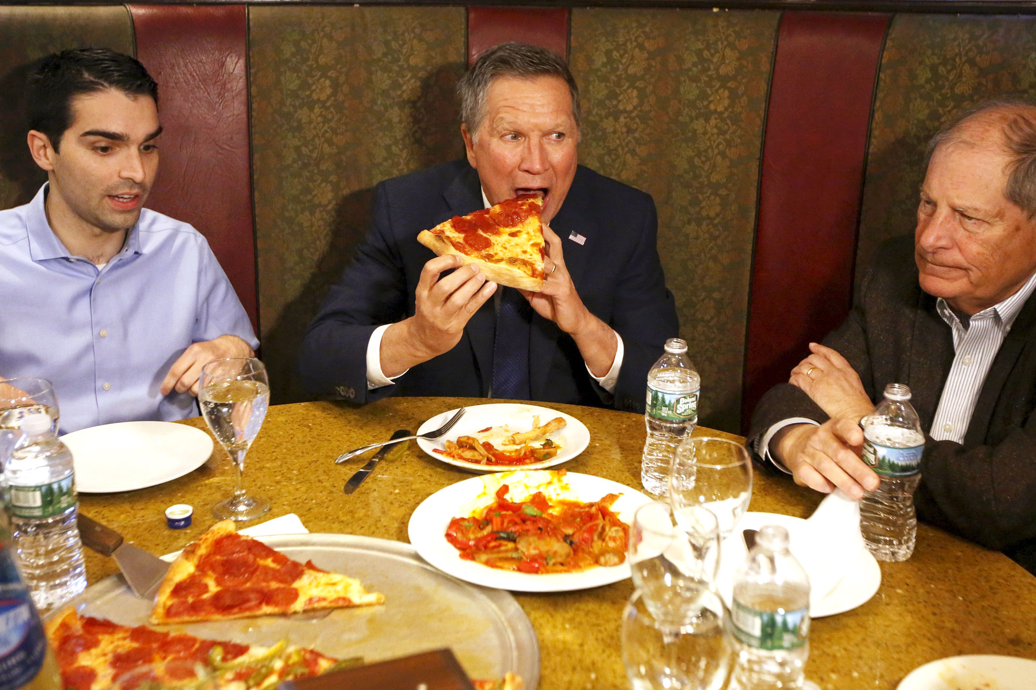 Republican presidential candidate, Ohio Gov. John Kasich eats a slice of pizza with Eric Ulrich, left, New York City Council member for the 32nd District of Queens, and former Congressman Bob Turner at Gino's Pizzeria and Restaurant in the Queens borough of New York on March 30, 2016.