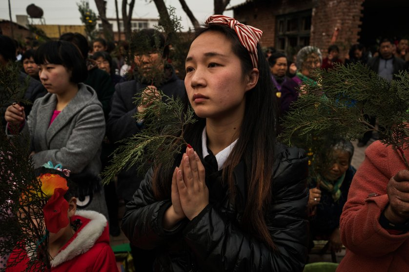 Parishioners clutch fir branches in place of palm fonds as they prey at an underground Palm Sunday service run by dissident Catholic Priest Dong Baolu in the yard of a house in Youtong village, Shijiazhuang, China, March 20, 2016.