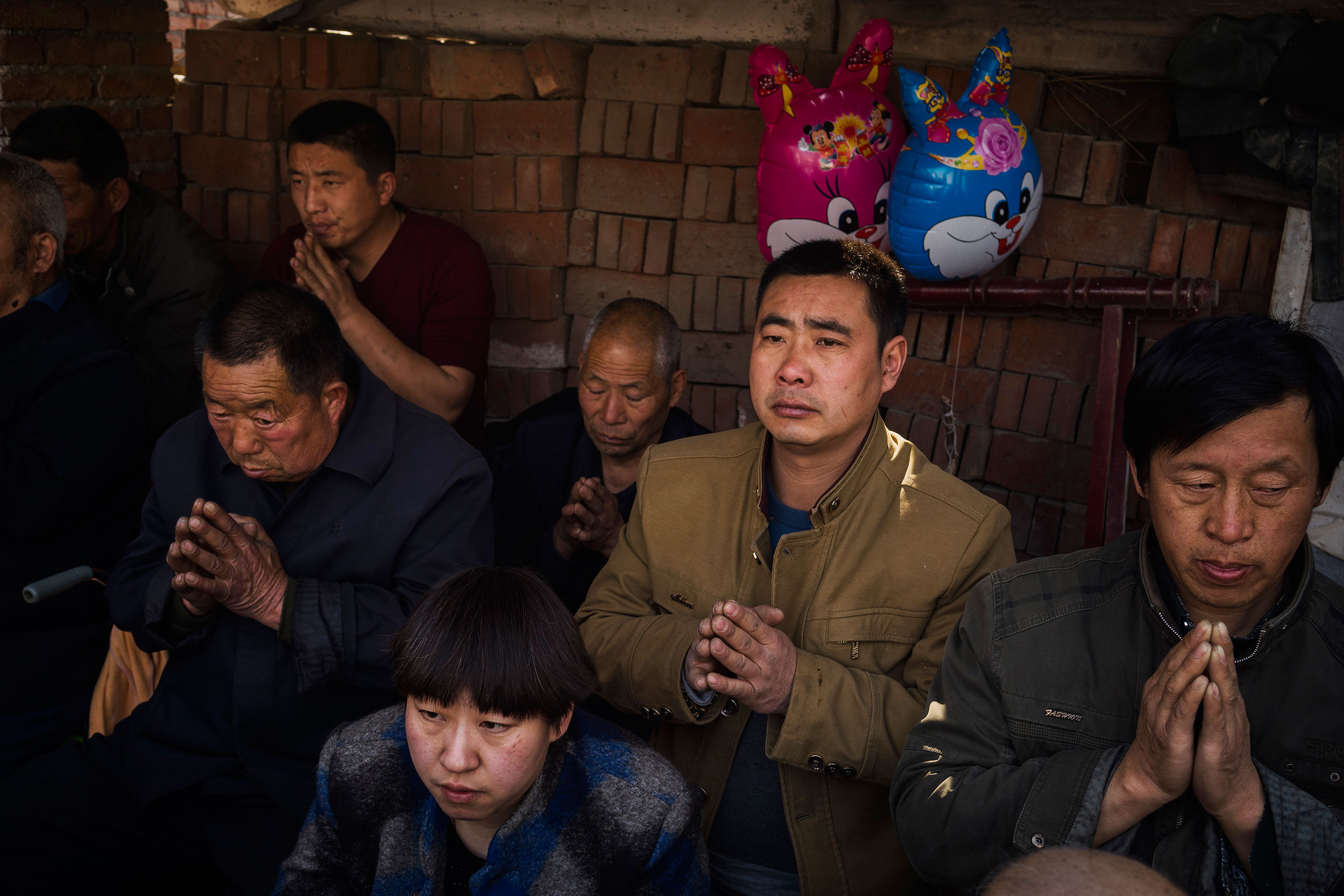 Villagers pray at an underground Easter Sunday Mass led by dissident Catholic Priest Dong Baolu in the yard of his house in Youtong village, Shijiazhuang, China, March 27, 2016.